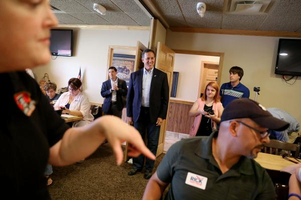 Former Pennsylvania Senator and 2016 Republican presidential candidate Rick Santorum prepares to speak while waitress Stacia Hall, of Anamosa (left) takes an order at McOtto's Restaurant in Anamosa on Wednesday, July 15, 2015. (KC McGinnis / The Gazette)
