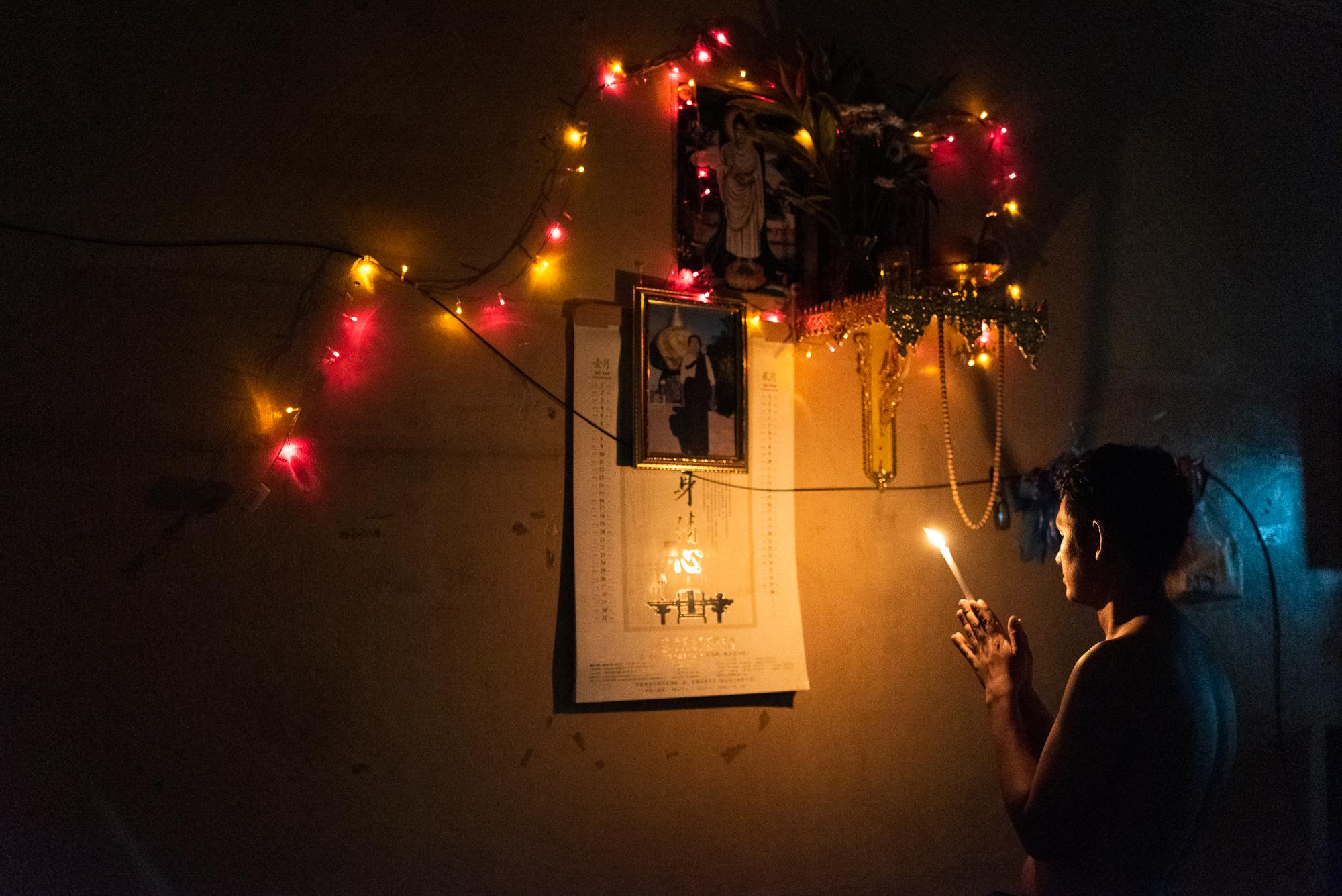 BANGKOK, THAILAND – NOVEMBER 30, 2018: Aung Myo Thun, a Burmese worker from a village near Naypyitaw, Myanmar, praying in his apartment in Yaowarat, Bangkok's Chinatown. Under the Buddha's portrait is a photo of his old mother, who still lives in his hometown. He is one of Burmese workers who came to work in Thailand with hopes for a better future.