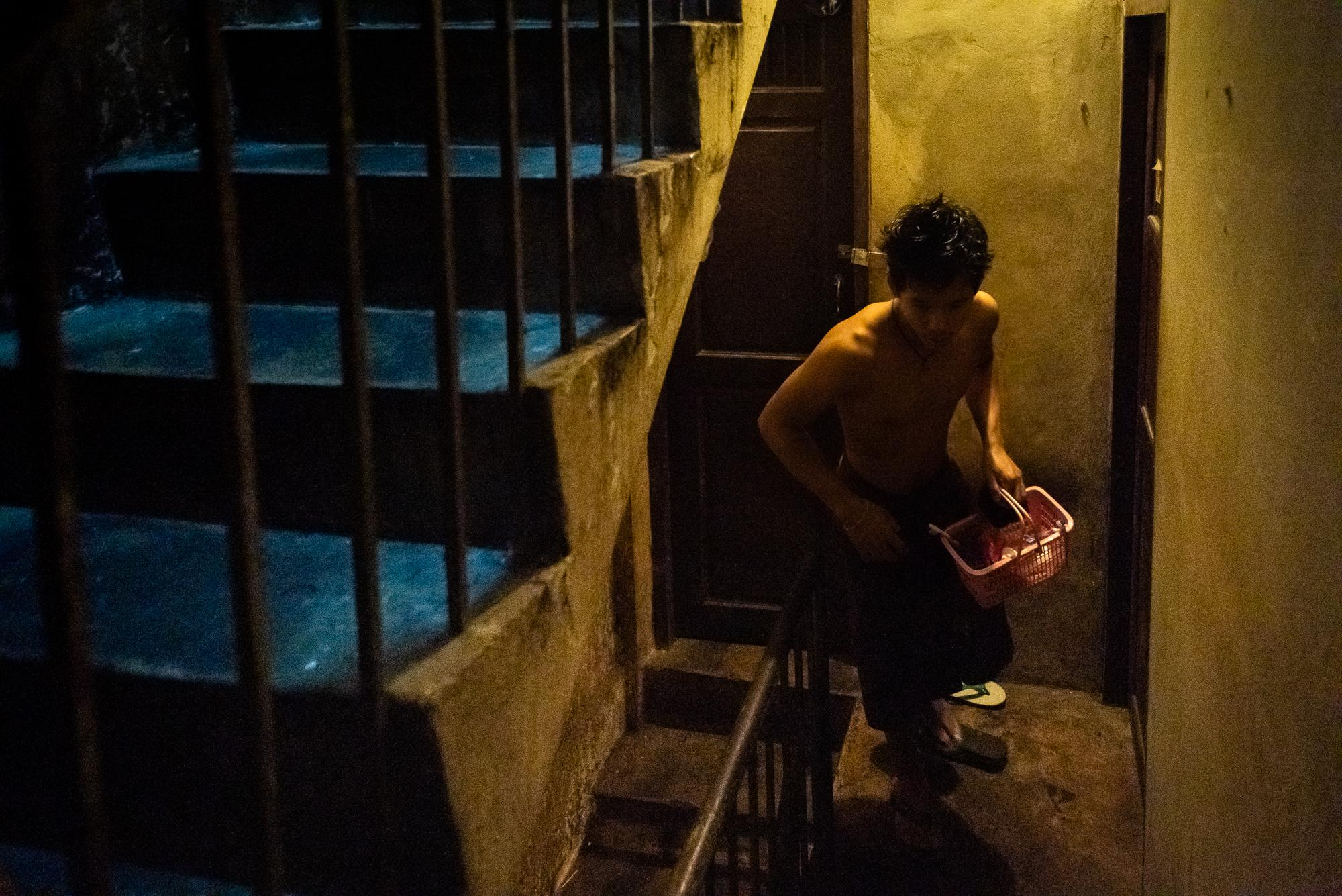 BANGKOK, THAILAND – SEPTEMBER 5, 2018: A Burmese worker carrying toiletries in a plastic basket walking back to his apartment after taking a shower in shared bathrooms.