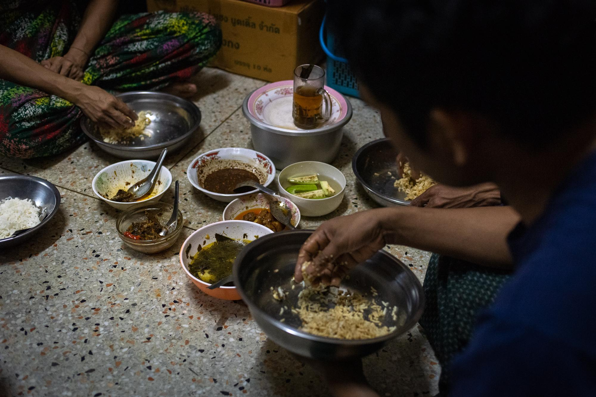 BANGKOK, THAILAND – DECEMBER 11, 2018: Most Burmese workers in Yaowarat prepare their own meals and eat at home, mostly Burmese food. Special ingredients from Myanmar can be found easily in Burmese grocery shops in the neighborhood. They usually eat by using hands, which is common in Myanmar.