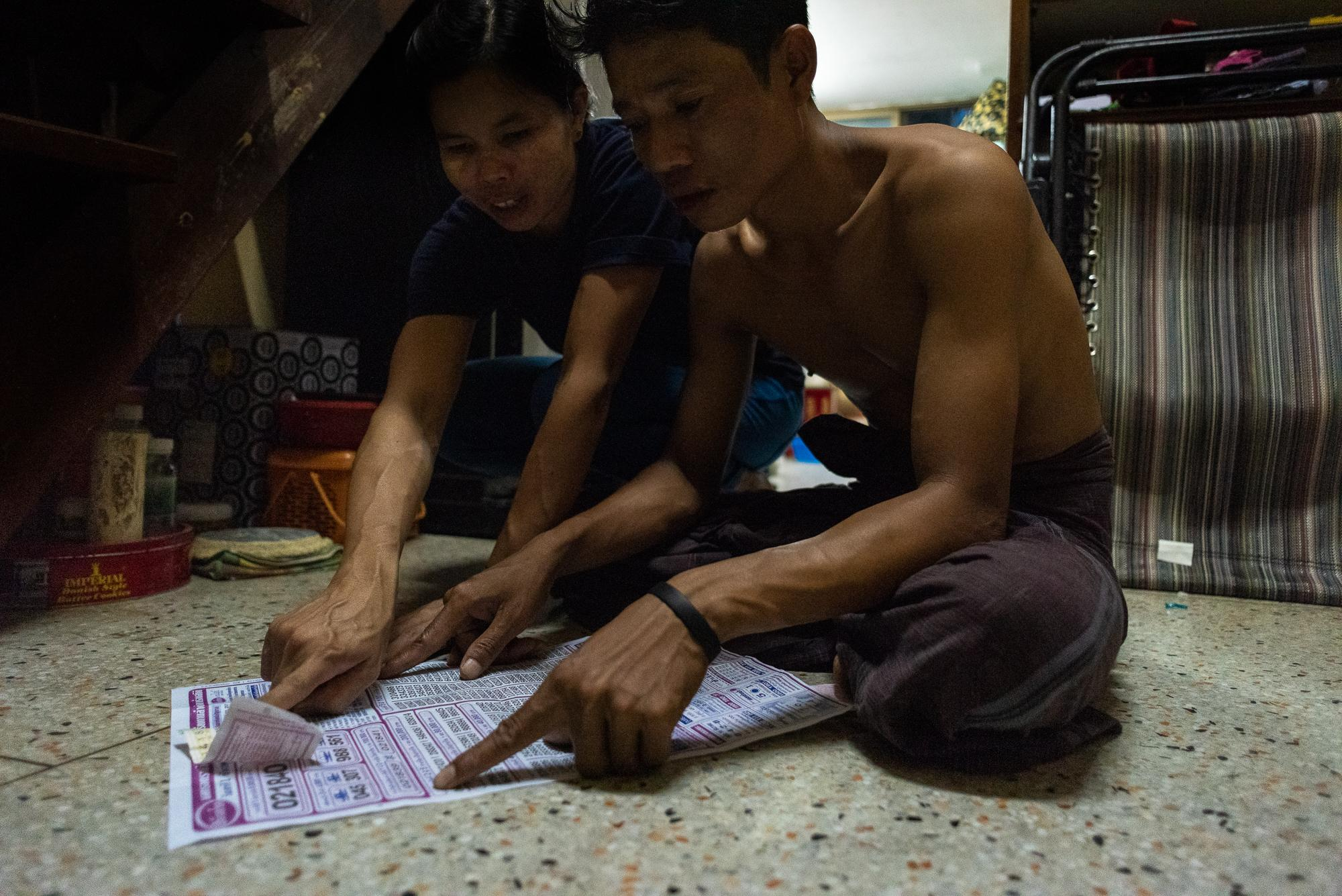 BANGKOK, THAILAND – DECEMBER 1, 2018: Zaw Min and his wife checking results of Thai lottery. They allocate a budget from their wages to play lottery every month. They have won prizes a few times after living in Thailand for two years.
