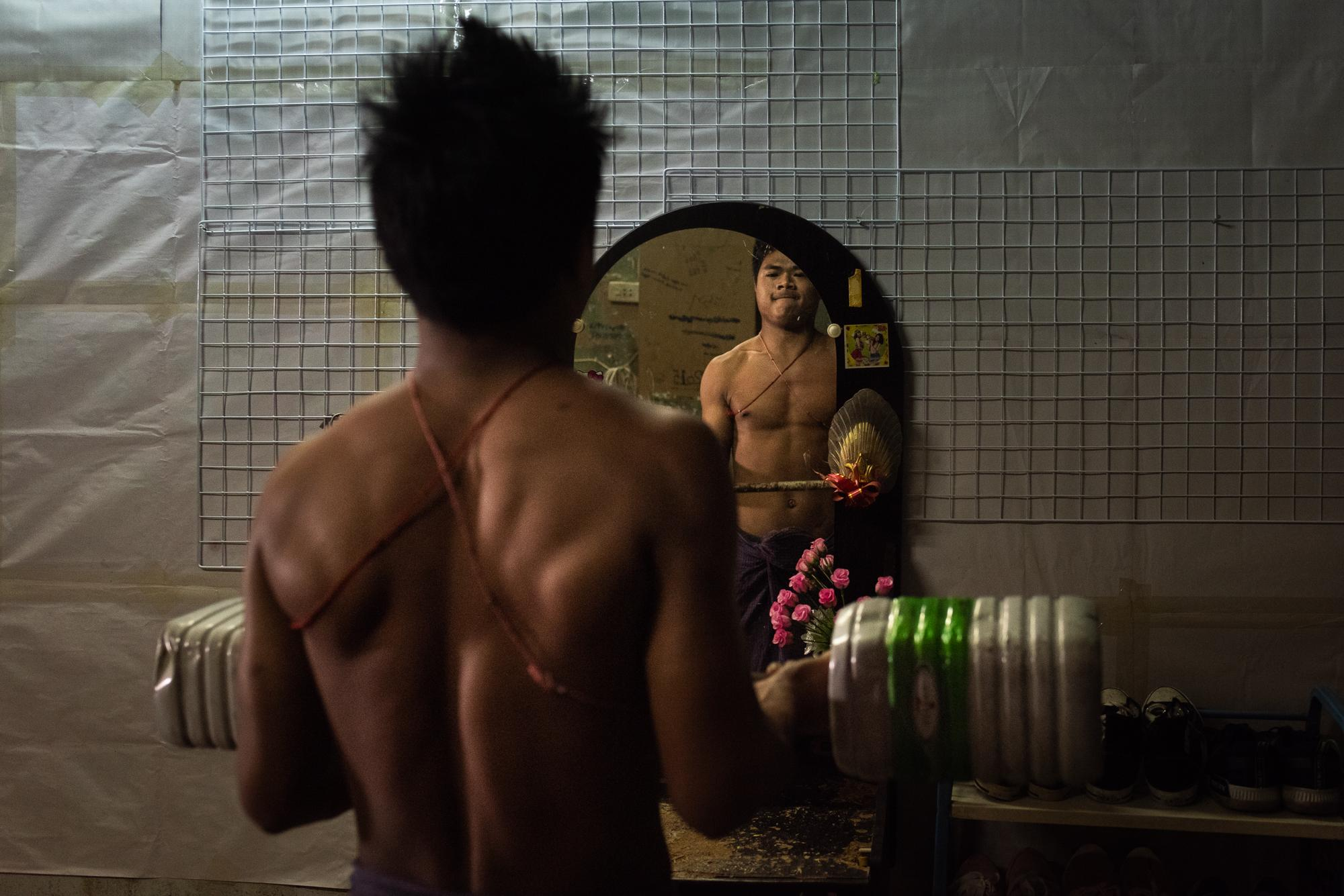 BANGKOK, THAILAND – DECEMBER 17, 2018: Aung Myat exercising with a barbell he made himself by filling plastic water bottles with sand. Keeping fit is important for Burmese workers, as most jobs that they get require physical labor.