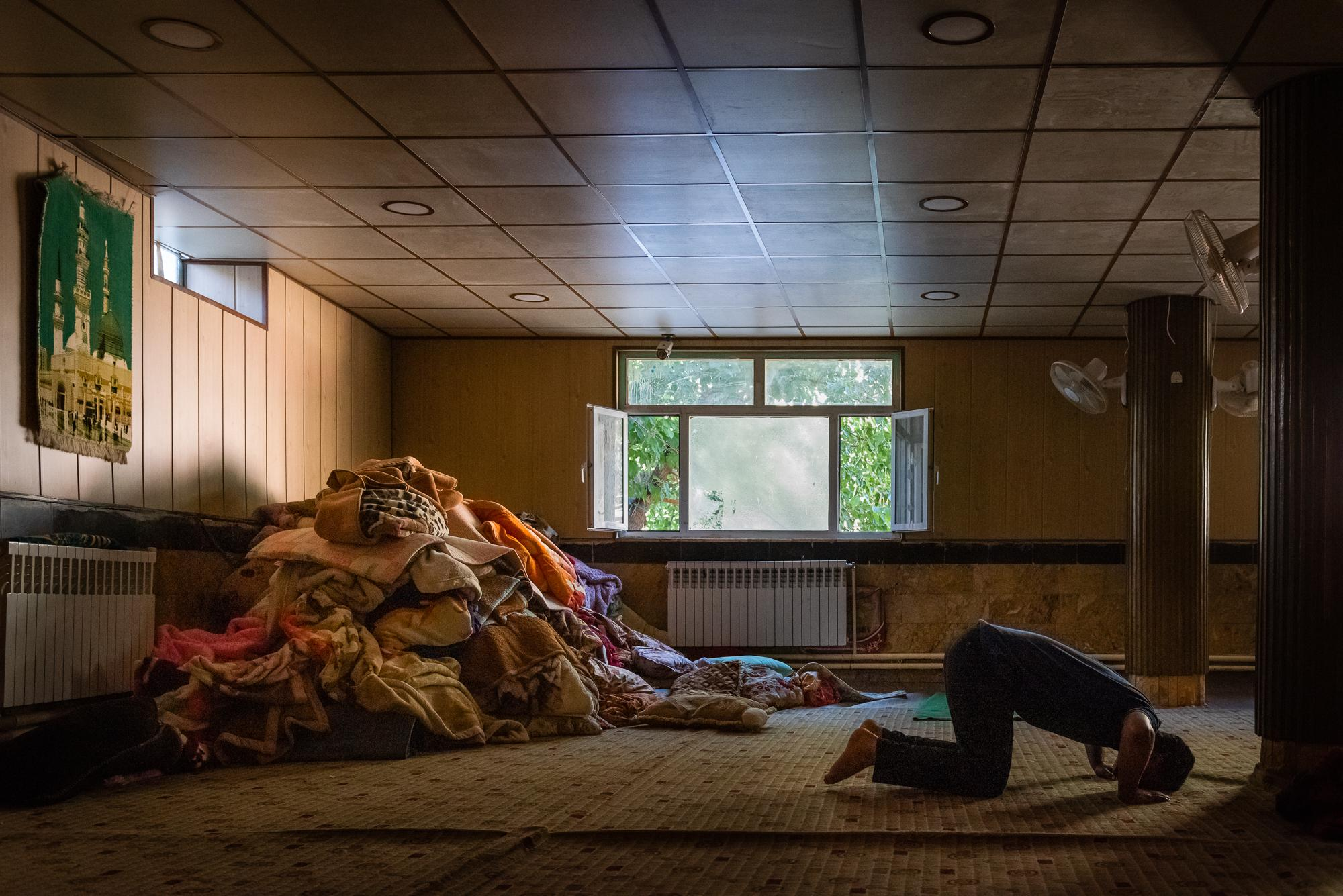 "BYARA, IRAQI KURDISTAN – SEPTEMBER 13, 2019: A man praying inside the sleeping hall of ""khanaqa"" (a building for gatherings of Sufi Muslims) at the Islamic School of Byara. It welcomes everyone from all walks of life, including non-Muslims, to eat and sleep while staying in this small Kurdish village close to the border with Iran."