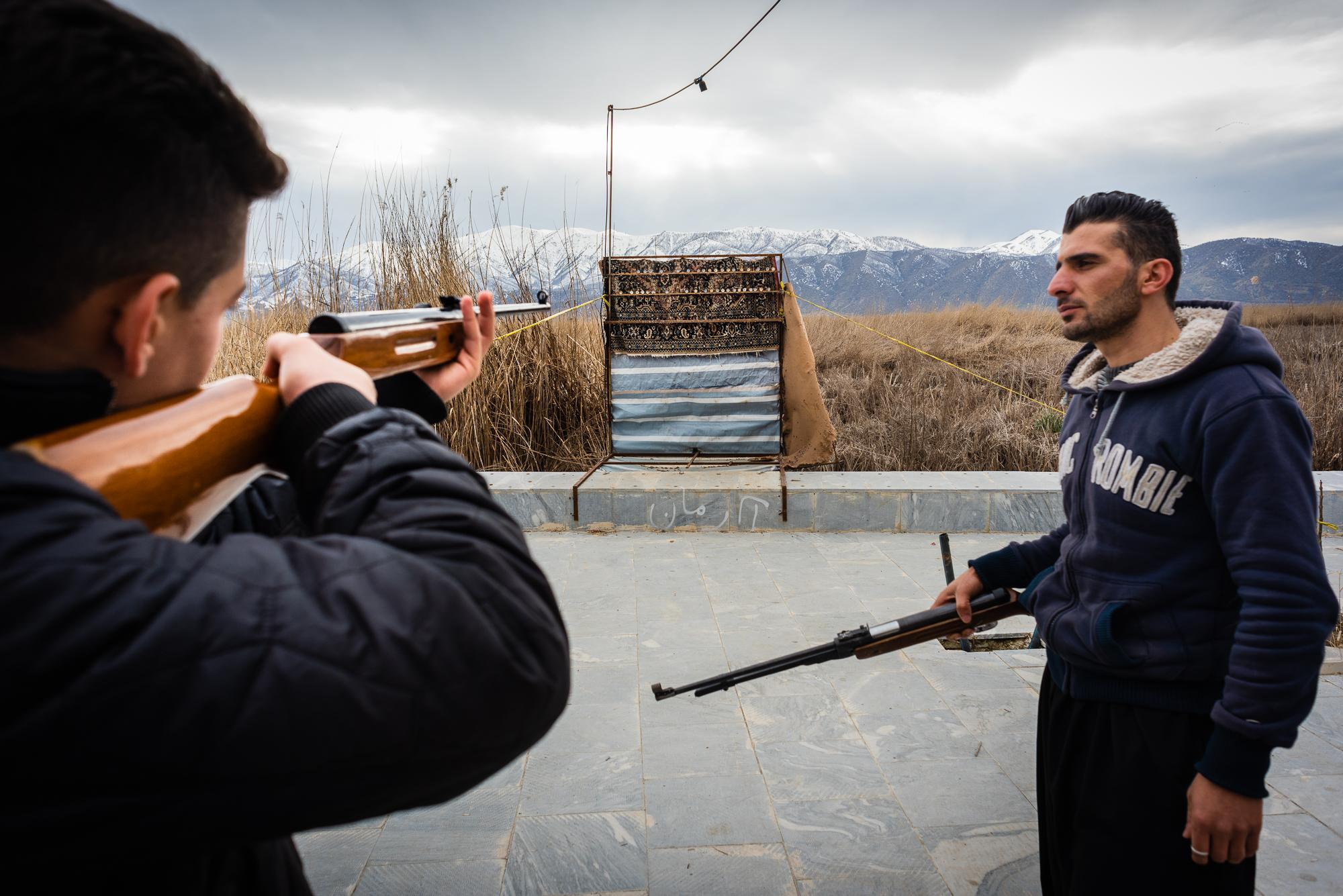 MARIVAN, IRAN – FEBRUARY 2, 2019: Young Kurds shooting air guns on the promenade along the Zrebar Lake.