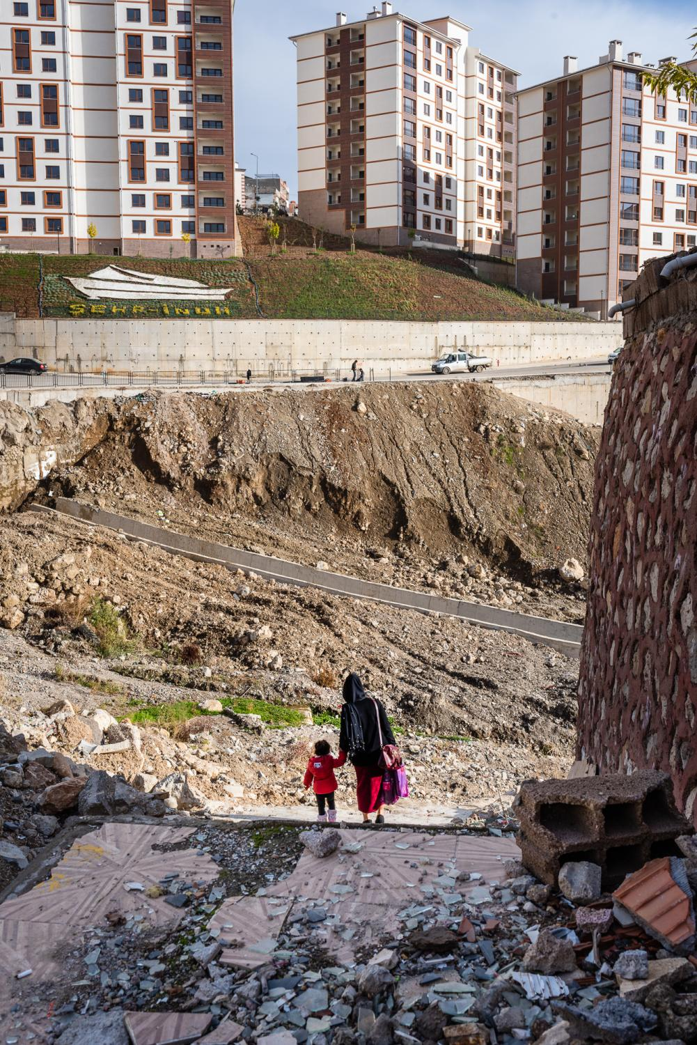 ŞIRNAK, TURKEY – NOVEMBER 20, 2018: A mother and her child walking pass a residential area which was a battleground between Turkish government forces and PKK rebels from 2015 - 2016. The clashes destroyed residential buildings completely. Rubble and bullet holes are still visible until today. In the background are new apartment buildings built by the Turkish government for affected families.