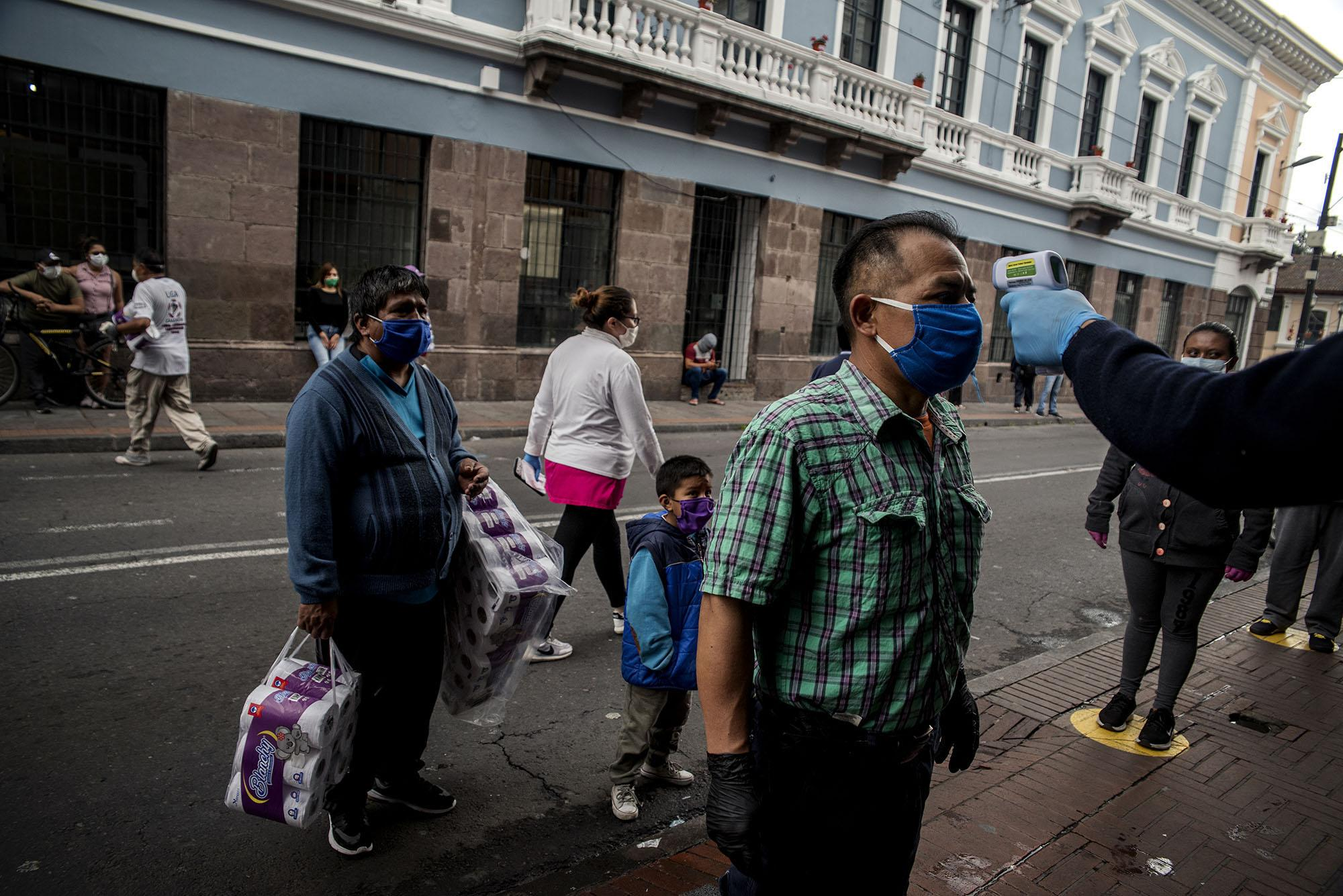 Supermarket guards control the temperature to allow their customers to enter. Thursday, May 7, 2020 in Quito - Ecuador. Johis Alarcón for The New York Times
