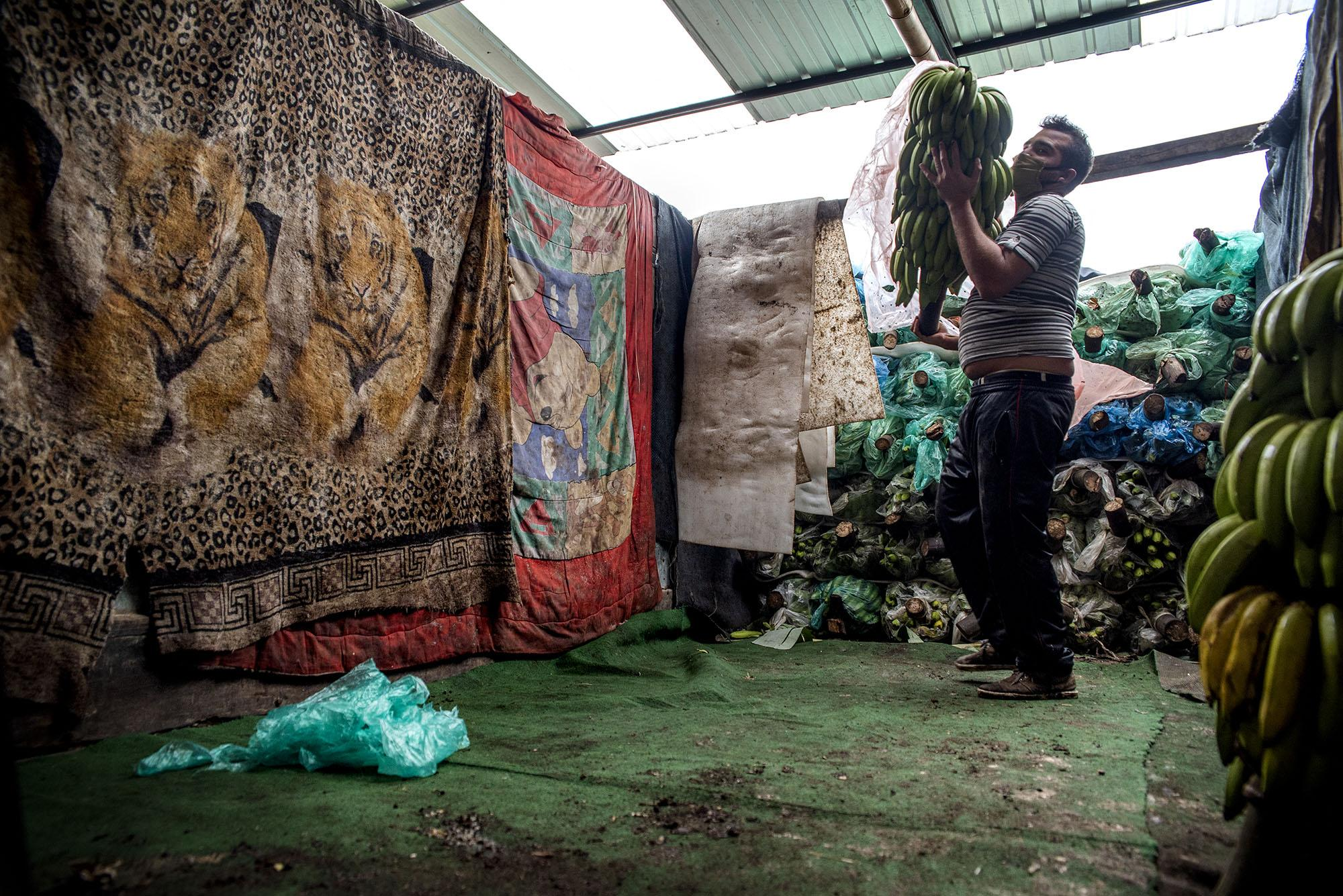 A banana seller unloads his products from the truck on Thursday, Abril 30, 2020 in Quito - Ecuador. Johis Alarcón for The New York Times.