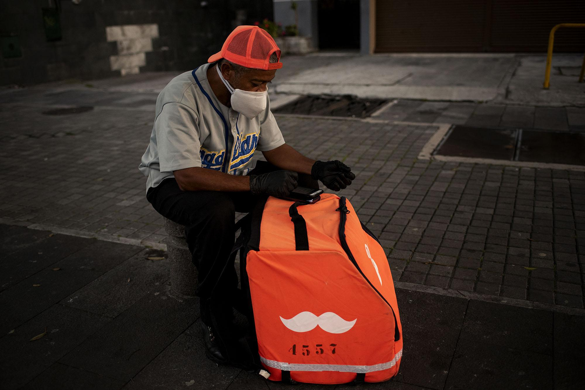 A home delivery worker waits for your next order on the streets near restaurants on Thursday, May 7, 2020 in Quito - Ecuador. Johis Alarcón for The New York Times