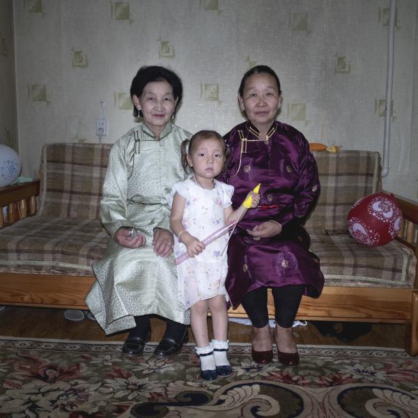 Tuya (64 anni), a sinistra, sua cognata e la nipote ritratte in abiti tradizionali (deel) nella loro abitazione di Ulaanbaatar. (Ulaanbataar. Mongolia, 2019) ©Simone Filpa