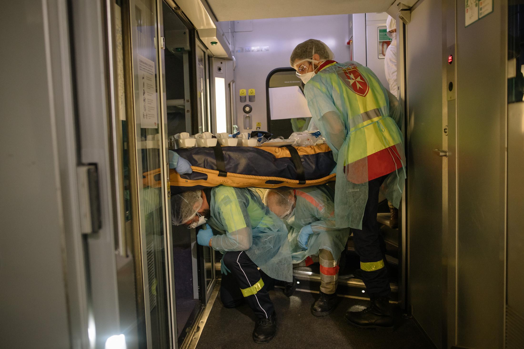 Paris. Gare d'Austelitz. Opération Chardon. Le 10 avril 2020. En tout, 45 victimes de toute l'île de France, vont etre transferées dans deux TGV en direction de Bordeaux et de Poitiers. L'objectif est de désengorger les hopitaux d'ïle de France saturés de patients en réa du covid-19. Un patient est transporté dans le wagon. Les secouristes bénévoles le portent. L'opération est périlleuse, il faut s'adapter aux angles du train.
