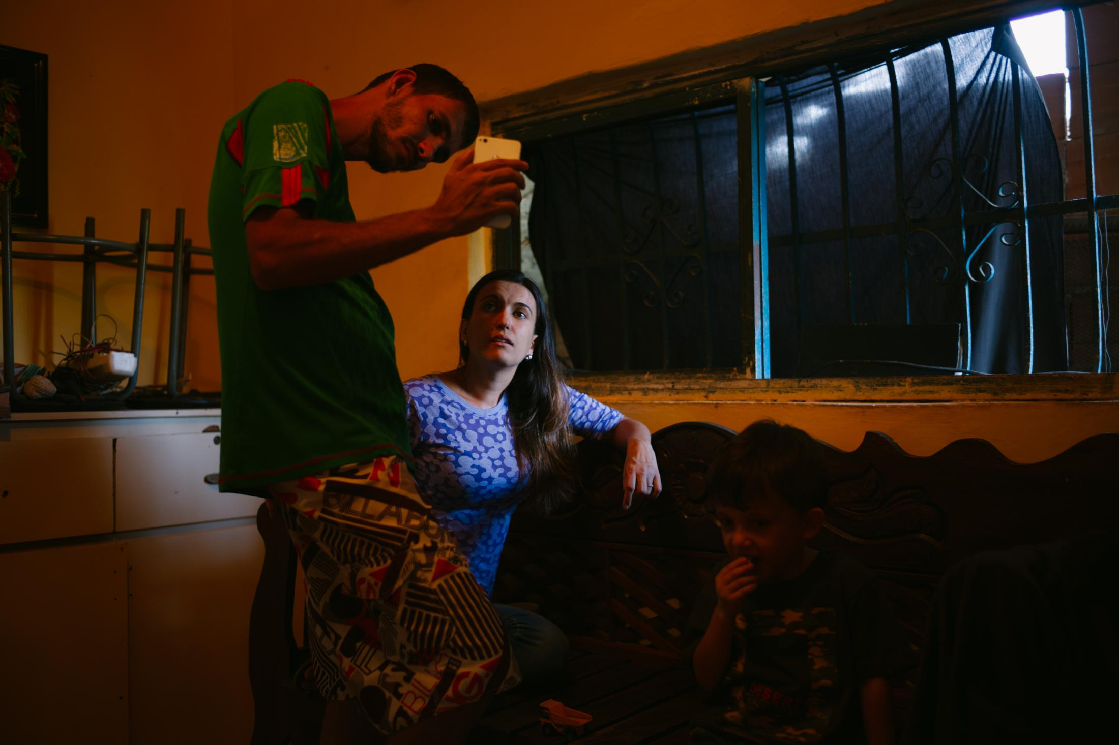 Francisco Aguiar (36) and Liseth Aguiar (31), both born in Venezuela, are video chatting with their parents and siblings who were already in Madeira. Liseth Aguiar died on May 10 2019 in Venezuela with hepatitis due to lack of treatment available in the country. Las Tunitas, La Guaira, Venezuela. 28th February, 2019. This was in the family house. Carlos and Rita (Liseth and Francisco´s parents) left it when they moved to Madeira in August 2017. The family is not only spatially divided: children of Portuguese immigrants are considered Portuguese in Venezuela, even if they were born there, and conversely, after decades abroad, Portuguese are considered foreigners when they return home.