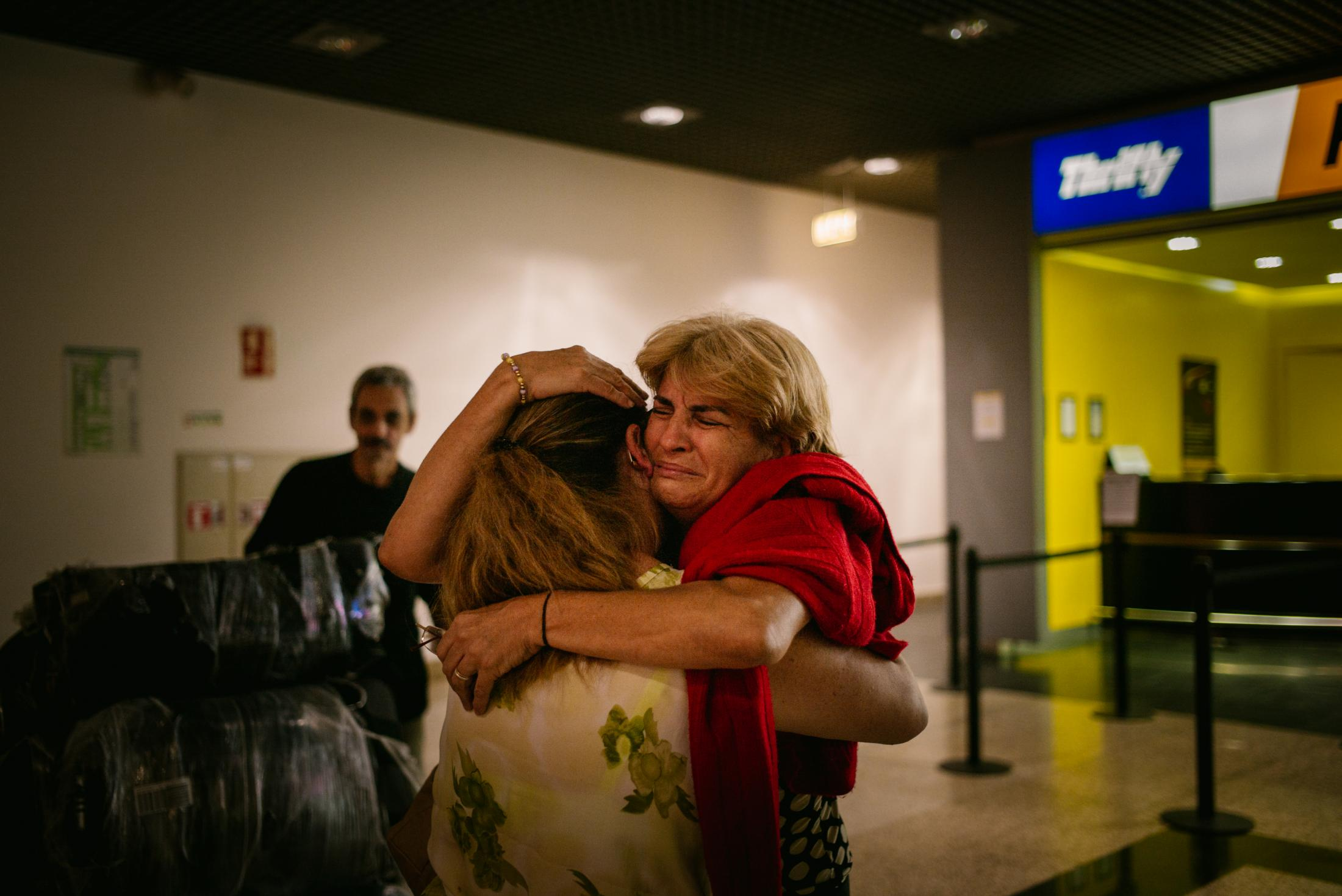 "On a Monday in August 2017, Rita Jardim Aguiar, 55, (seen from the front) and Carlos Aguiar, 64, (in the background) are welcomed by Rita's sister at the Funchal airport in Madeira. Madeira, Portugal. 21st August 2017. Carlos and Rita emigrated to Venezuela in 1981 chasing their ""Venezuelan Dream"". In August 2017 they had to abandon Venezuela. They left behind all they had fought for and their 3 oldest kids, including their daughter Carla Aguiar. Carla´s two youngest siblings (both born in Venezuela), Stefany (14) and Jhon (18) moved with Rita and Carlos to Madeira. After Chávez´s death in 2013, Nicolás Maduro came to power and the number of returnees to Madeira has increased significantly since then. Maduro has transformed the country into a dictatorship and brought it into a crisis: Food and medicines are scarce, the infrastructure is dilapidated, and the electricity is always cut. Rita and Carlos saw no future in the country for themselves and their family."