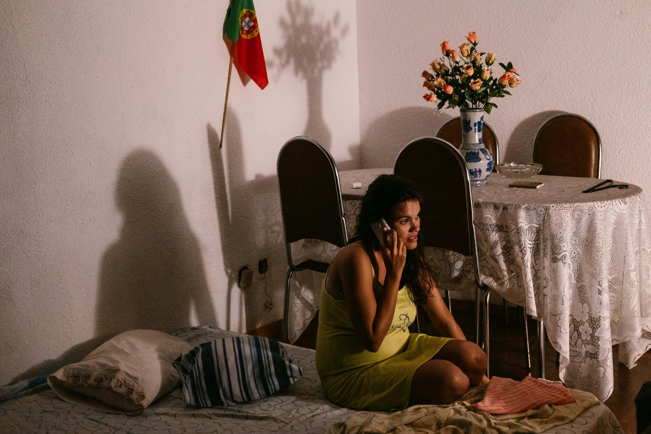Carla Aguiar (28) sits pregnant, at her mattress in the lIving room at her parents home in Camacha. She is on the phone with Josué Artiaga (36), her husband, who, at that time, was still in Venezuela. Camacha, Madeira, Portugal. 16th August 2018. At the time the family was trying to save money to move Josué to Portugal on time before their baby ́s birth.