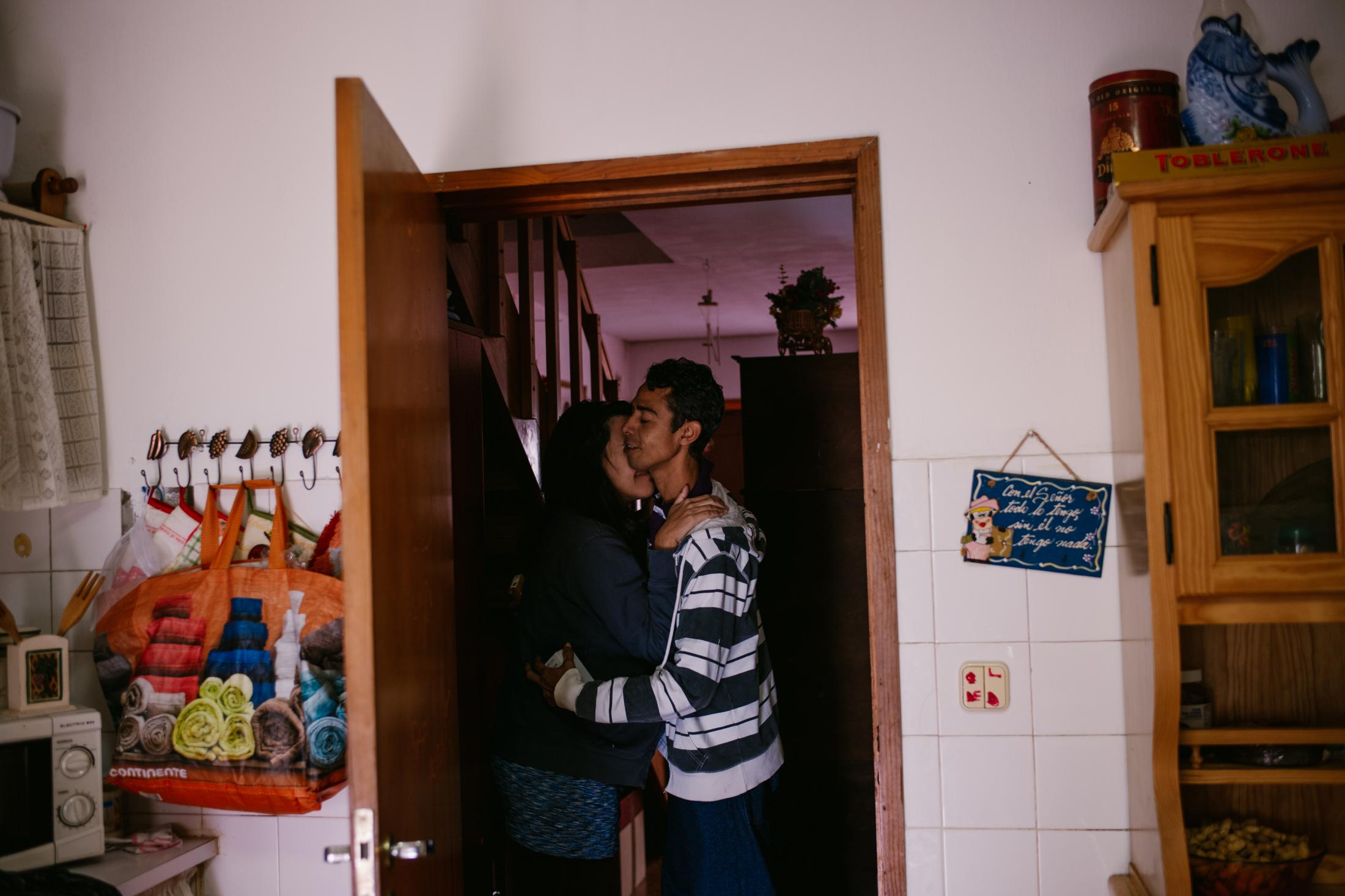 Carla hugs her husband Josué at her parents ́ home. Camacha, Madeira, Portugal. 28th December 2018. Josué moved to Madeira late November to meet his wife again and to start a new life in the Portuguese Island. Both of them were born in Venezuela and neither of them speak Portuguese.