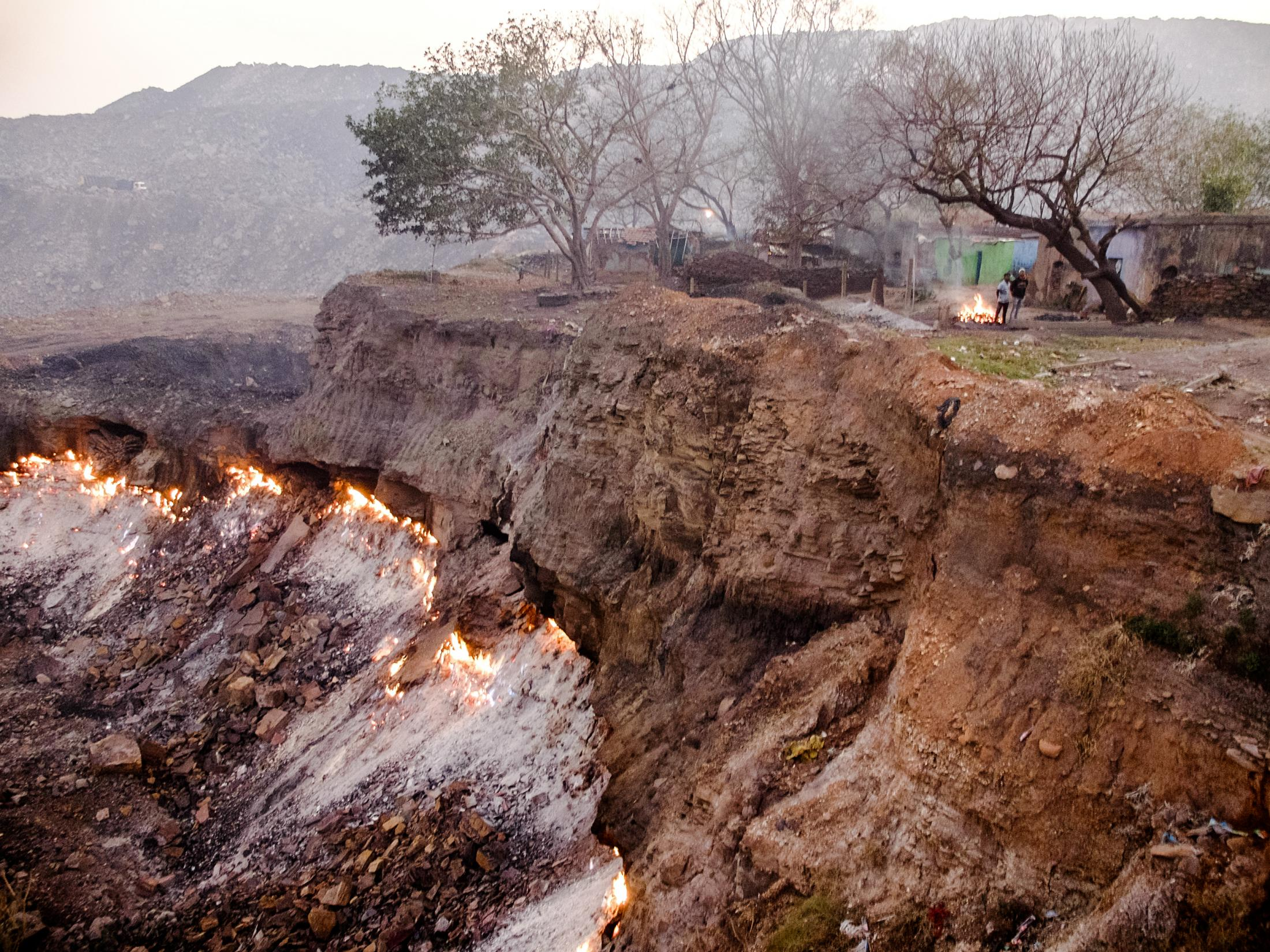 Flames break through the ground from coal fires that burn underground at an open cast mine in Laltanganj village. Many of the villagers are relocated to Belgaria as part of the goverment's help program, but some of the villagers refused to go. India 2020