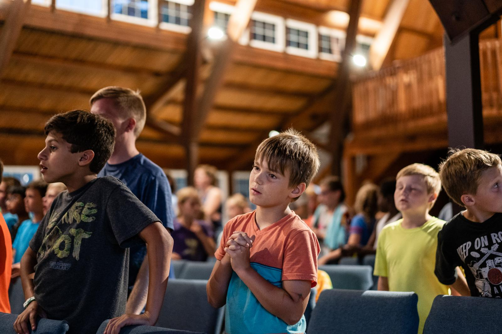 A camper prays during a chapel session at Riverside Lutheran Bible Camp in Story City, Iowa on Tuesday, July 16, 2019. ©2019 KC McGinnis