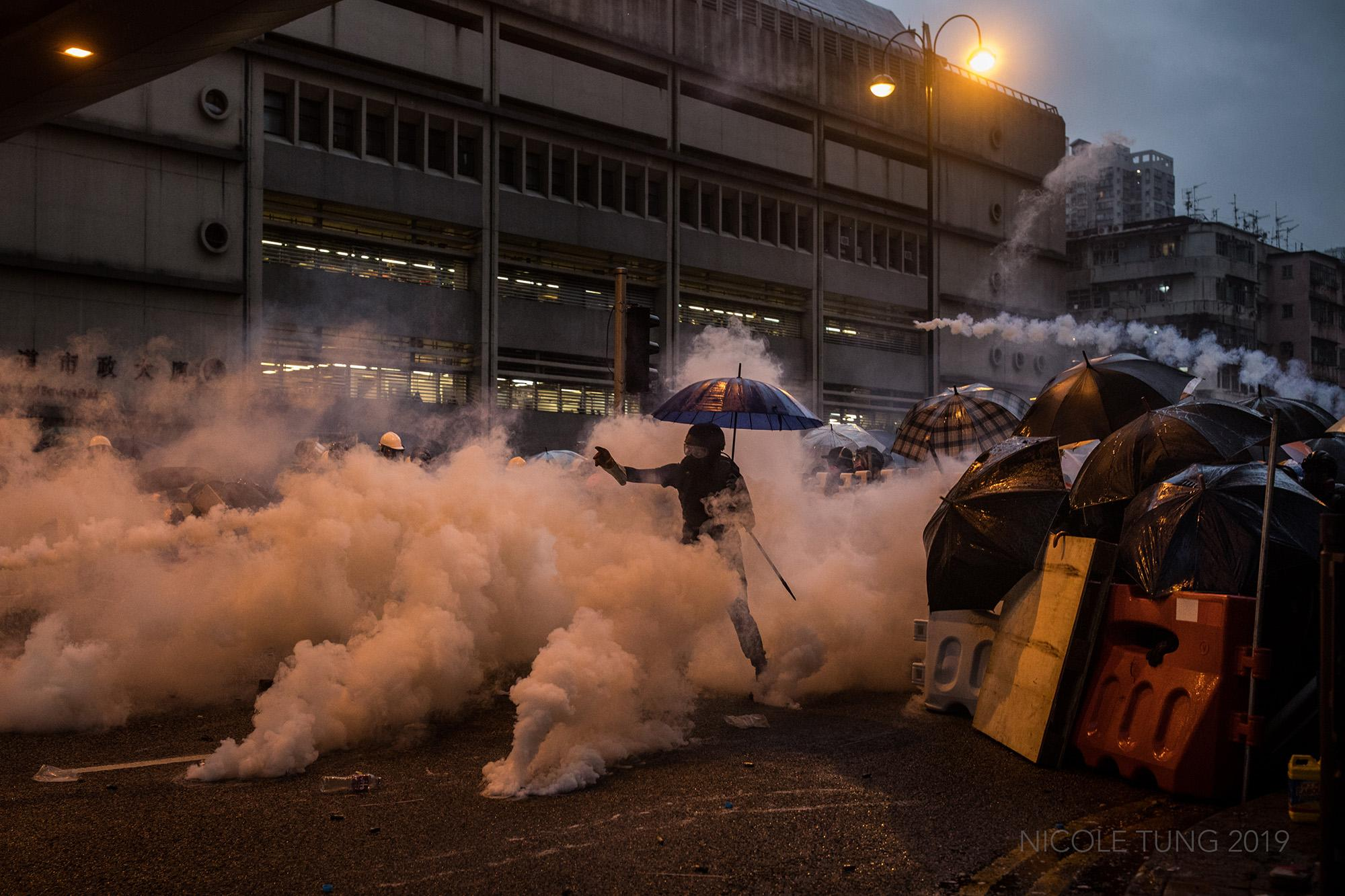 A protestor throws a tear gas canister back at the riot police in Tsuen Wan neighborhood in Hong Kong, S.A.R. following the end of a rally in which thousands participated. August 2019.