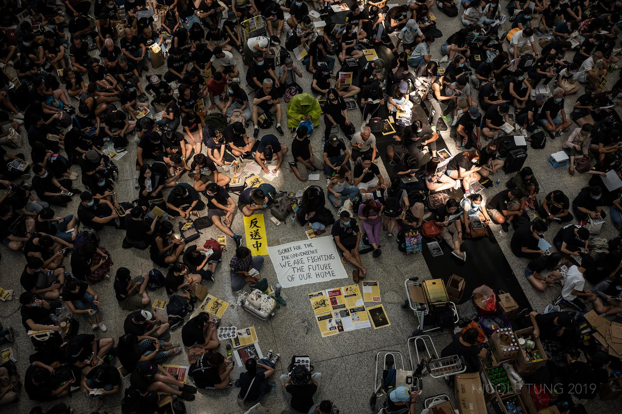 Protestors staged a sit-in at the arrivals hall of the Hong Kong International Airport in Hong Kong, S.A.R. on the first of their three day sit-in at one of Asia's busiest transportation hubs. Protestors hope that their campaign at the airport would help spread the word and launch a mass appeal to international travelers and the media about why demonstrations were continuing in Hong Kong and what people seek from the government. August 2019,