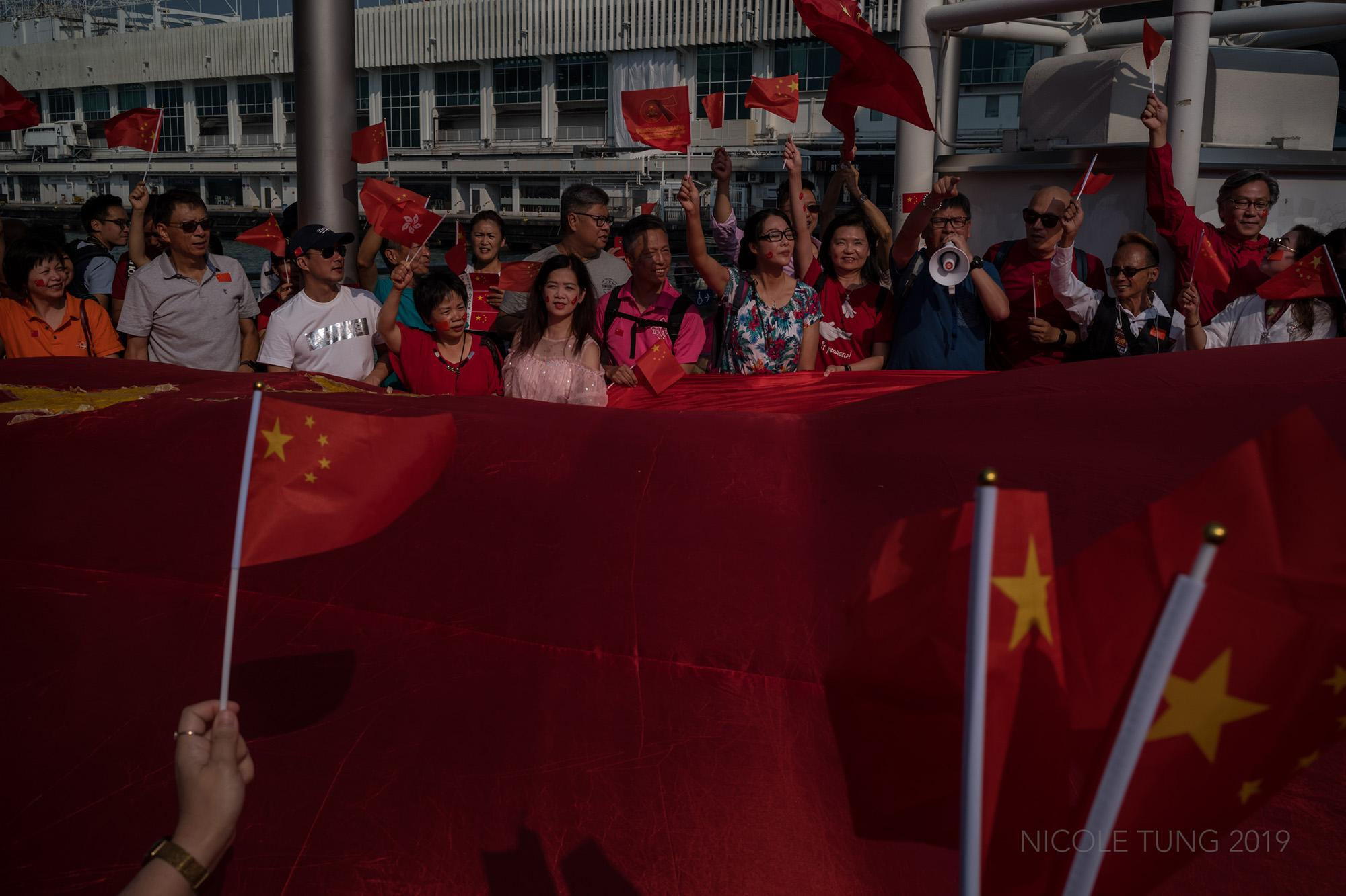 People celebrate the 70th anniversary of the Peoples' Republic of China as several dozen people joined a gathering to show their support of the Chinese government despite concerns that anti-government protests would continue on the day, in Hong Kong, S.A.R. October 1, 2019.