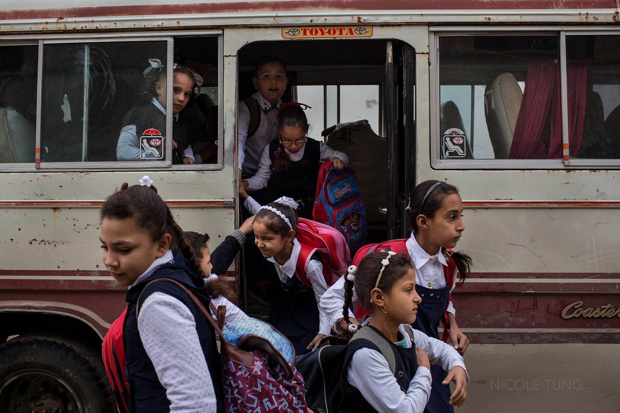 Schoolchildren exit a bus in western Mosul, Iraq. Since Mosul was declared liberated by the Iraqi forces four months ago, some schools have reopened in the city where many children have missed years of their education. November 2017.