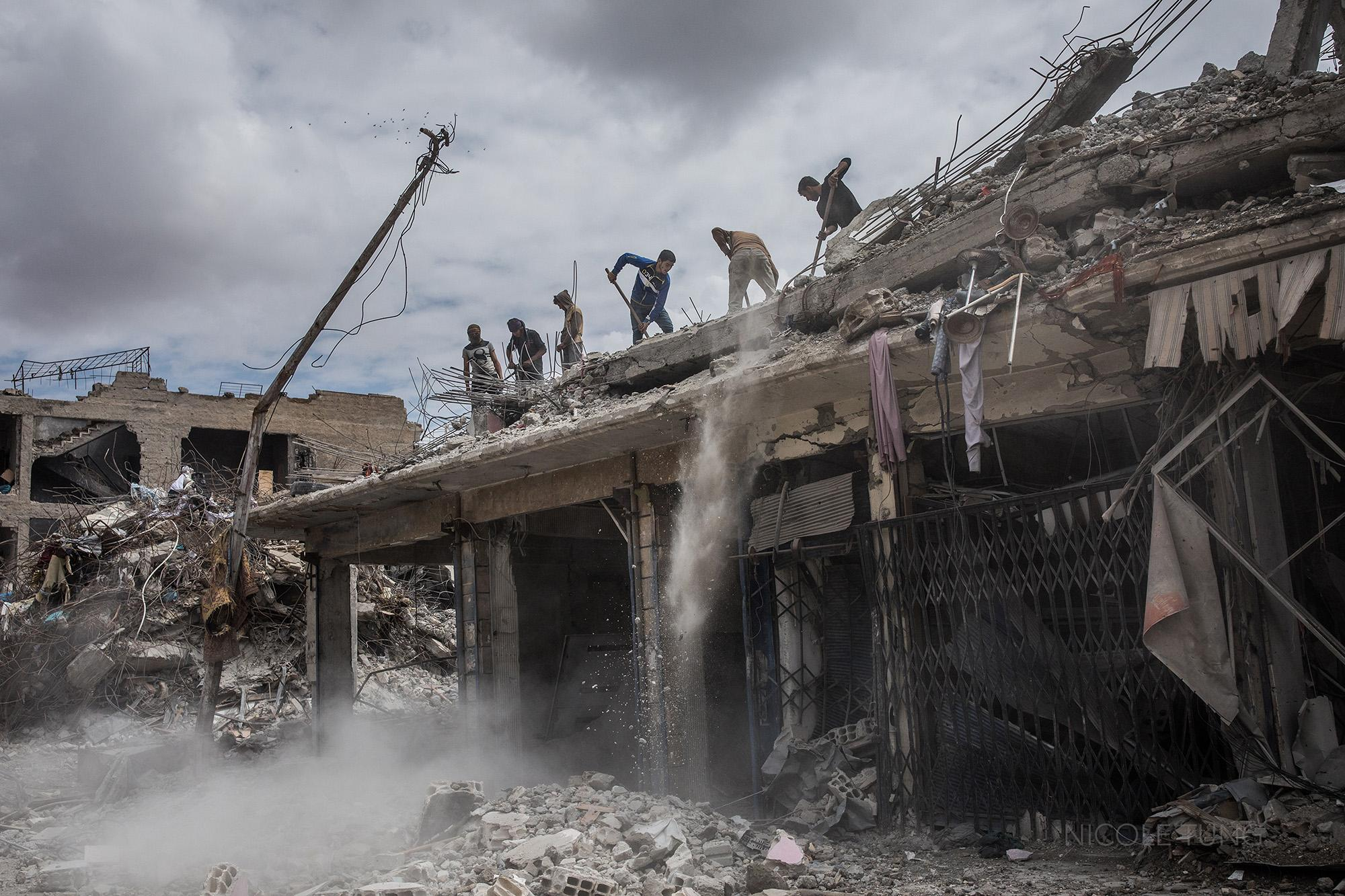 Construction workers remove rubble from a destroyed building in Raqqa, Syria. May 2018. An estimated 80 percent of Raqqa's infrastructure was destroyed or damaged during the offensive to retake the city from ISIS, with thousands of lives lost in aitstrikes by the coalition, addition to those civilians who were executed by ISIS during their reign over the city from 2014 until their ouster in 2017.