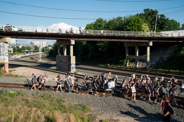 Protesters take over train tracks, march to Raleigh Central Prison.