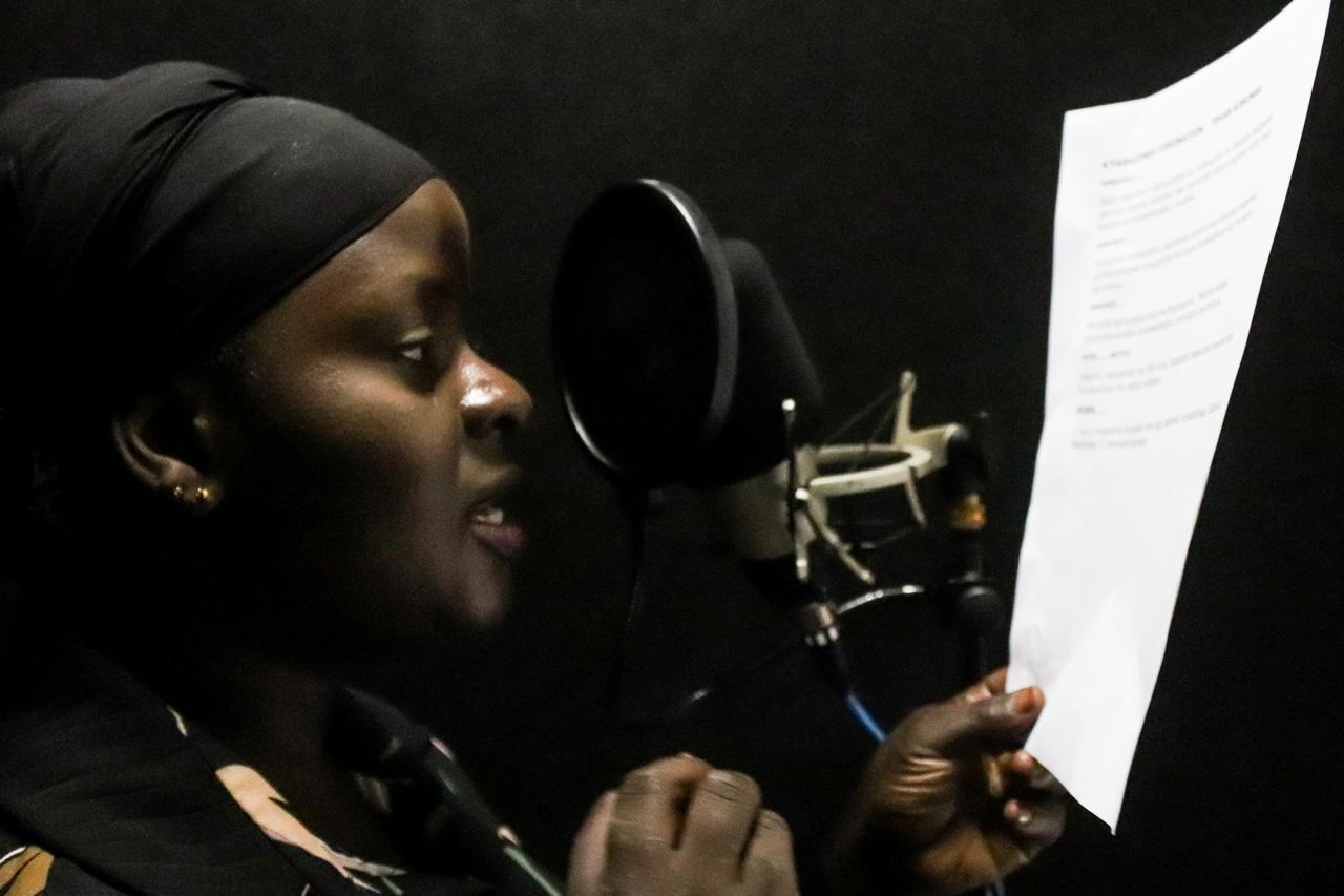 Luganda News Reporter Aminah Nabukenya, voicing her story in preparation for the 'Amasengejje' bulletin, a Luganda-language news show that airs daily on weekdays. Owing to its accessibility, the bulletin is popular with people in Kampala and central Uganda.