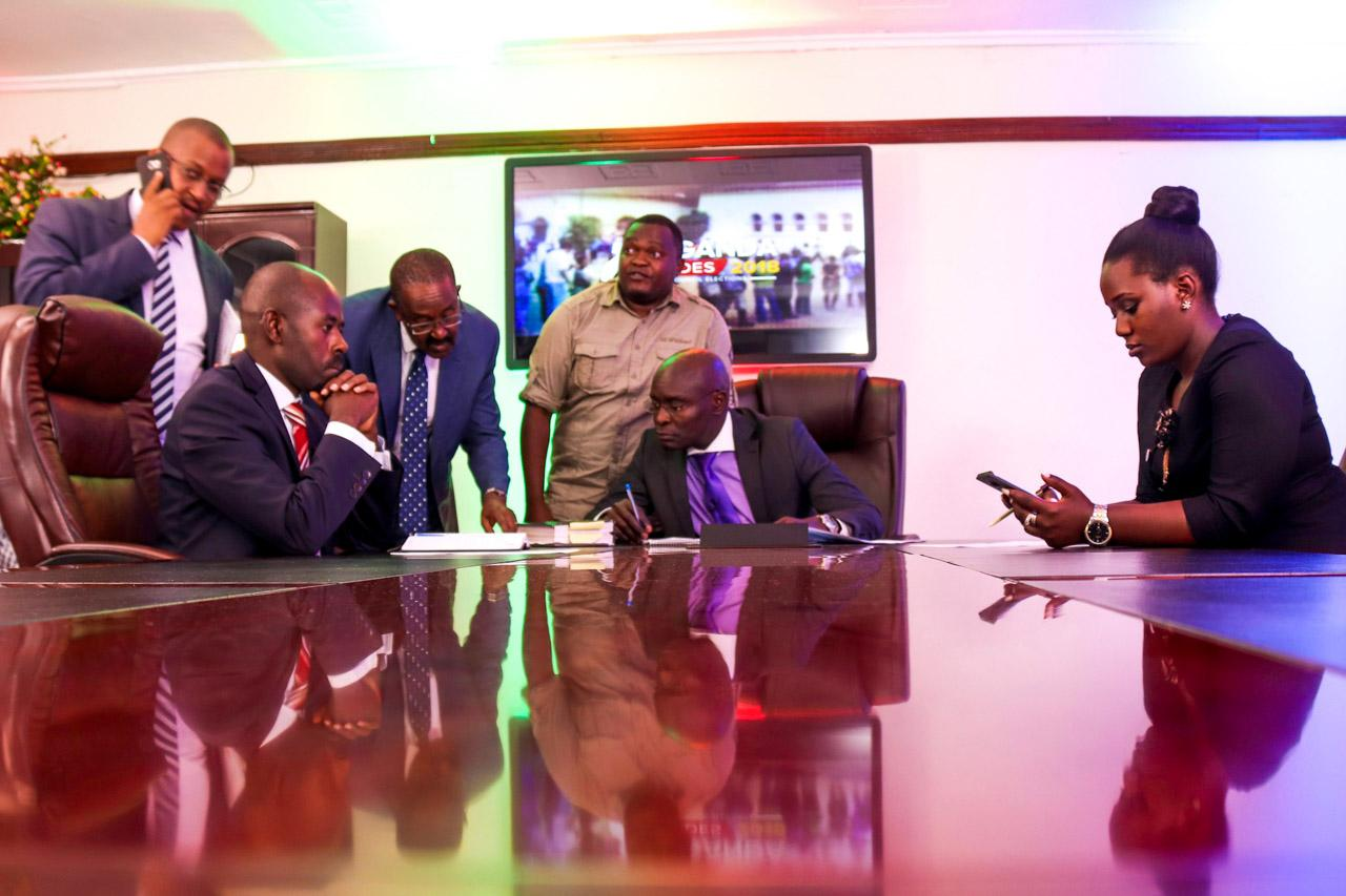 Justice Simon Mugenyi (centre), who heads the electoral commission in Uganda, engaging in a small meeting with presenters and show producers in preparation for a live broadcast on Uganda's electoral plan.