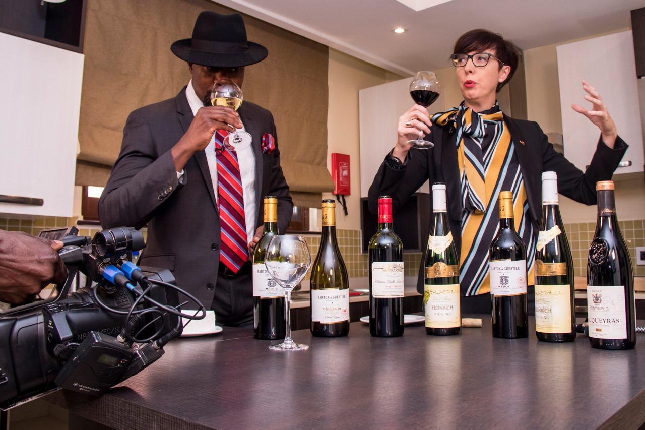 News Anchor -Samson Kasumba (left) takes a sip of sweet white wine, during filming of a program with the then Ambassador of France to Uganda -Stephanie Rivoal as she described how the French take their wine. The program is a partnership between the French Embassy and NBS Television.
