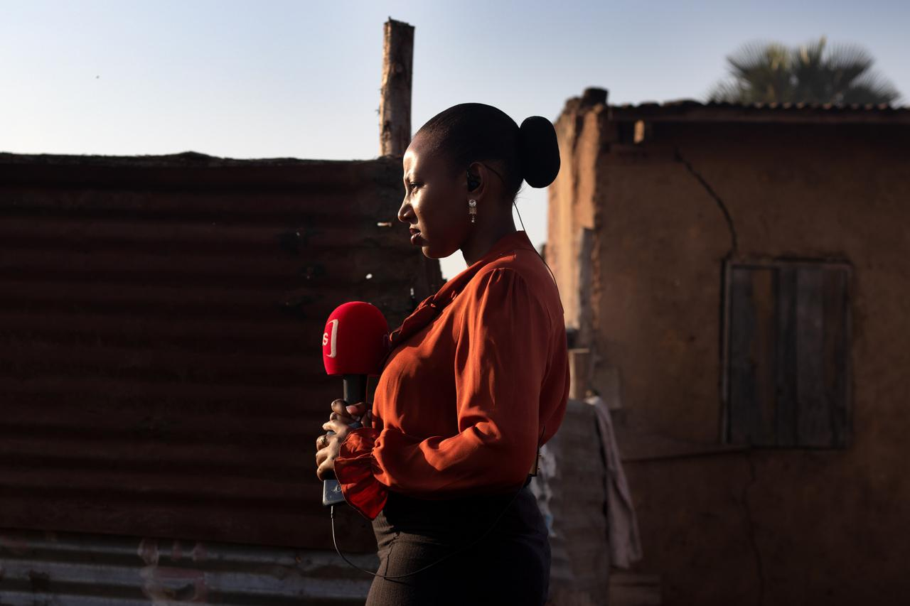 News Reporter -Victoria Bagaaya, on standby in Kikaramoja slum, Kampala, minutes before she goes live on the 'Morning Breeze' show.