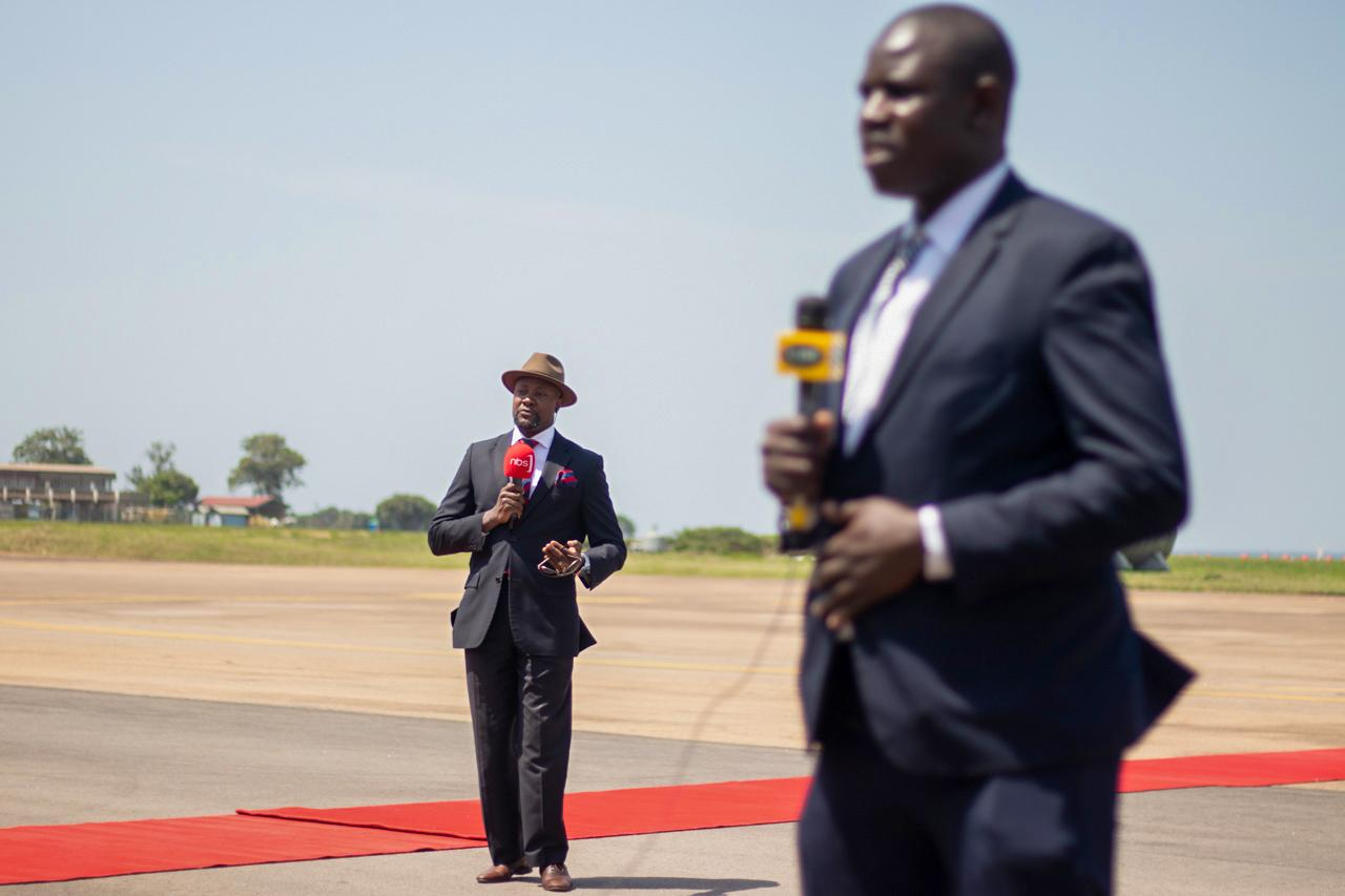 Senior Reporter and News anchor Samson Kasumba, with a UBC Television reporter, at the Entebbe airport tarmac, reporting live updates on the arrival of the Indian Prime Minister -Narendra Modi to Uganda om 24 July 2018.