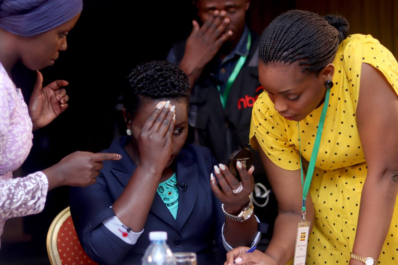 Senior Journalist -Mildred Tuhaise (center), refreshes her make up during a short break in filming, as her director (in yellow dress) takes her through the key points for the next segment.