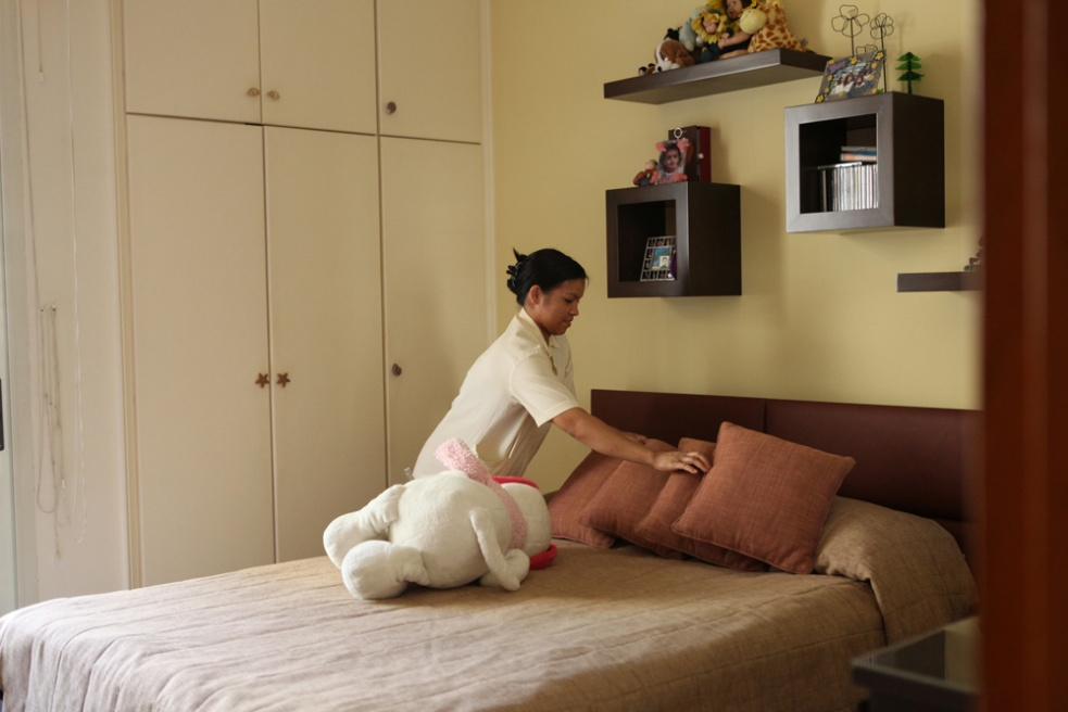 Sabina, from the Phillipines, tidies up her employer's daughter's bed at their family home in Beirut, Lebanon.
