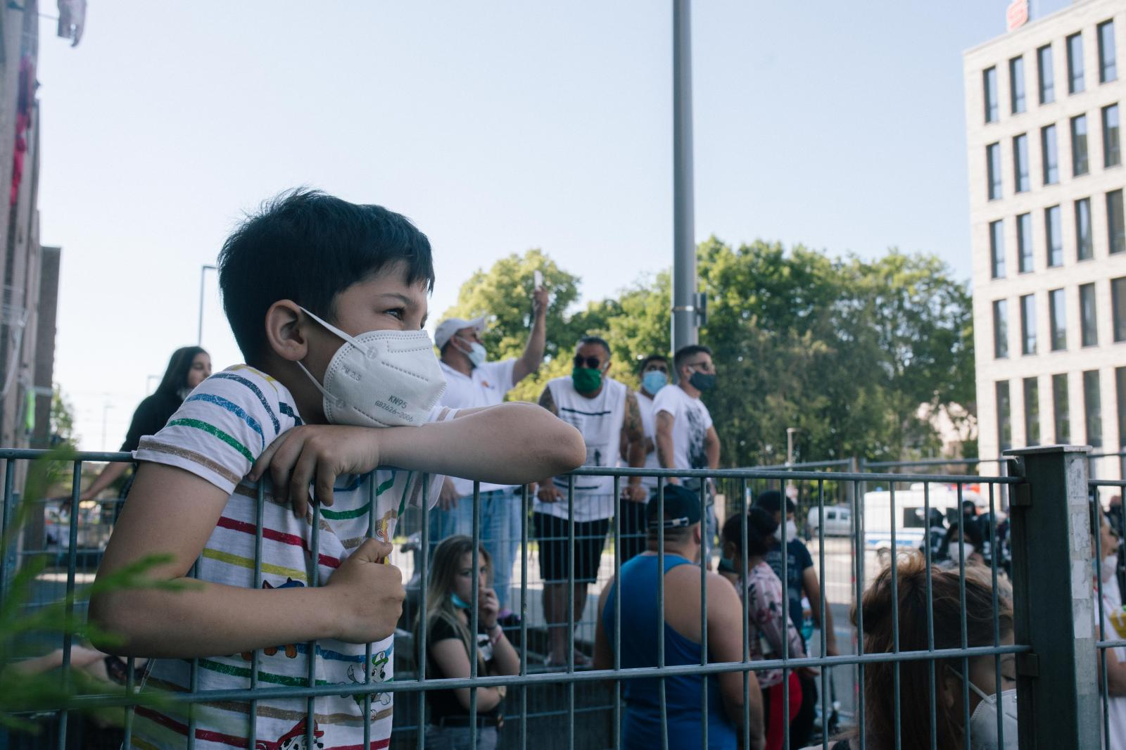 A young boy watches the solidary demonstration and police, standing on a fence. June 23rd
