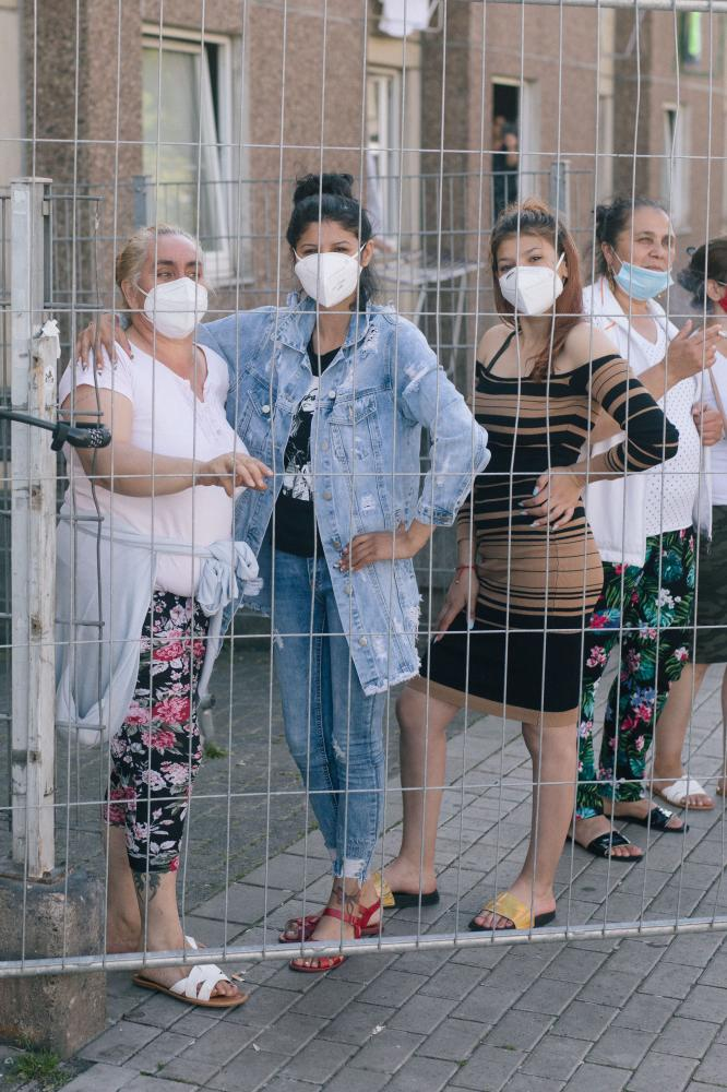 A group of inhabitans, that wish to stay anonymous, pose with protective masks behind the fence of Groner Landstrasse. June 23rd