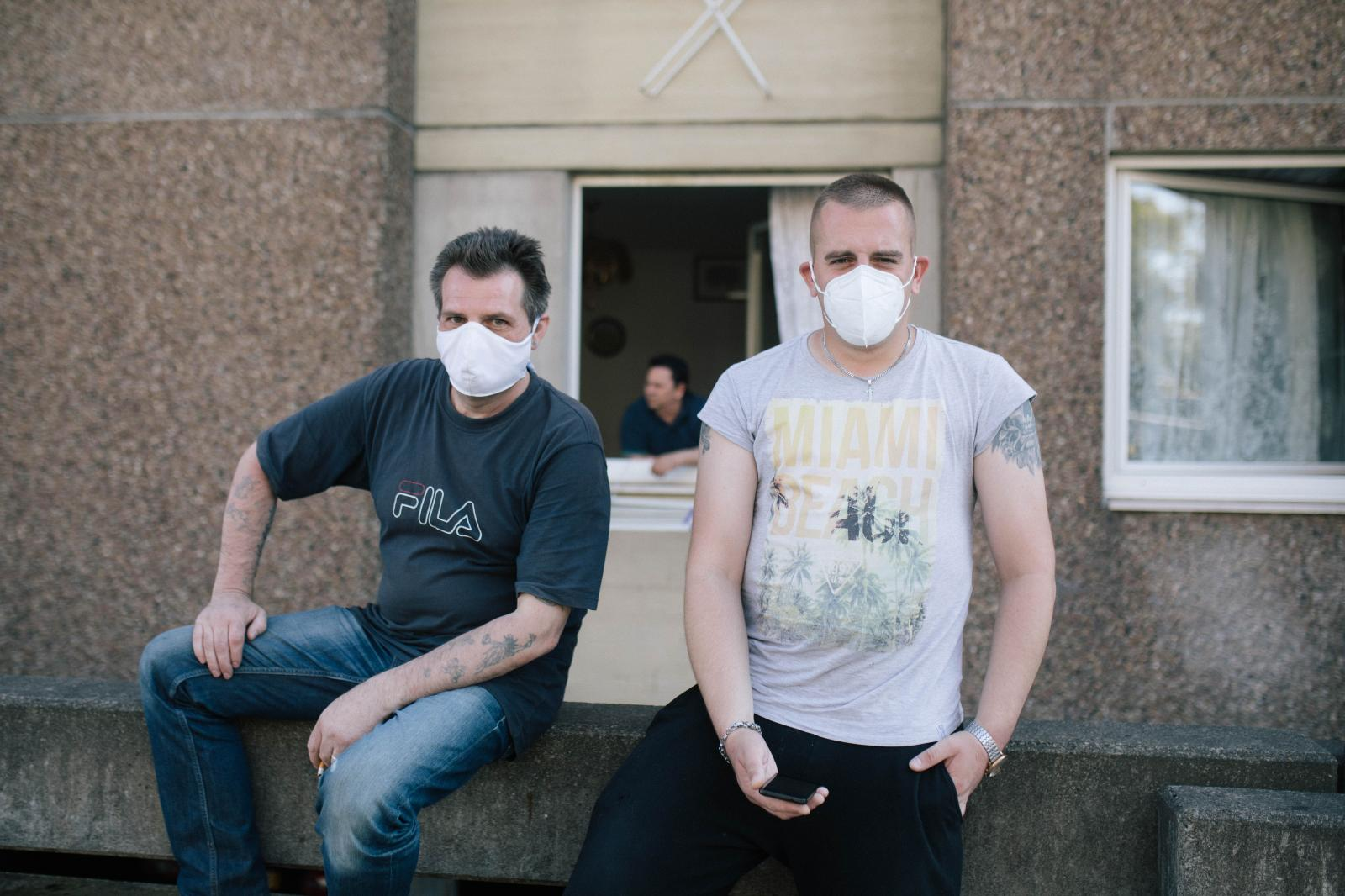 Two men, who want to stay anonymous, pose for a portrait in front of the building. One says that mildew is all over his appartement and that this has been going on since years. The city supplies the room to him. June 23rd