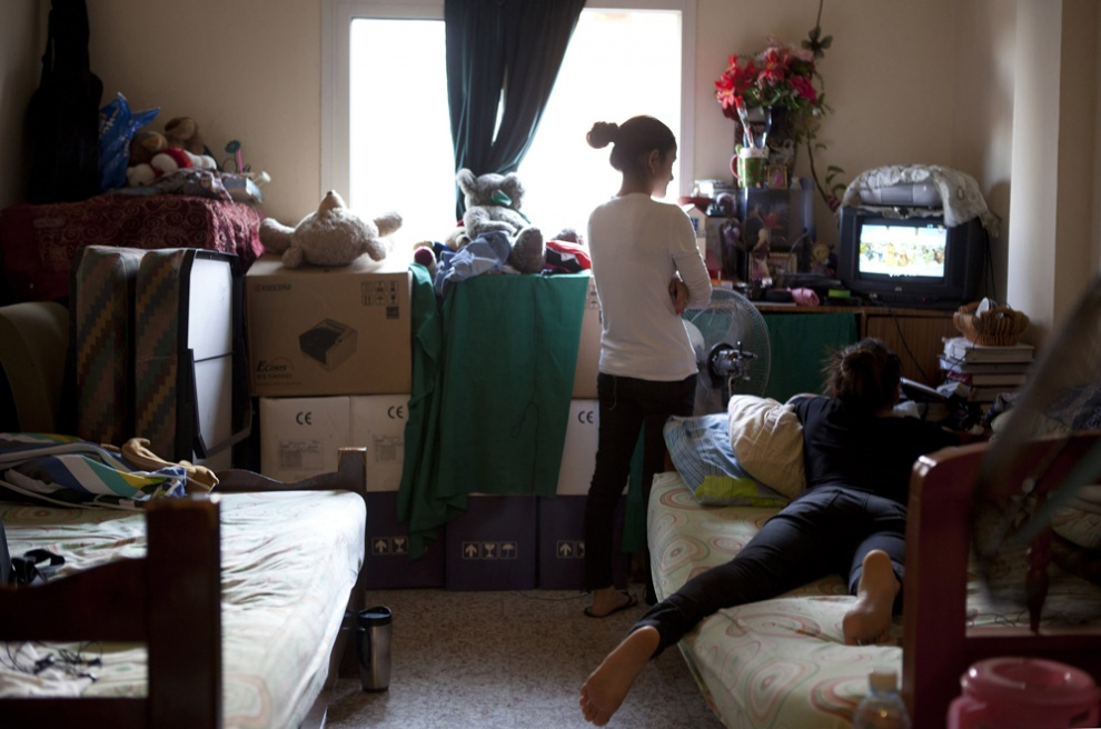 Two of the seven Nepalese young ladies who ran away from their employers, who live together watch television in their one bedroom flat on the outskirts of Beirut, Lebanon.