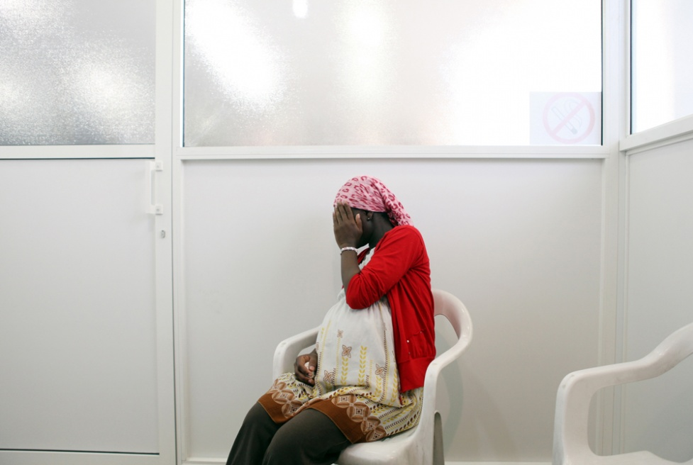 """Najat, 23, from Ghana, sits in an interview room at the Caritas Migrant Center in Lebanon. Her dream was to become a teacher, but her father could not afford her university fees. She came to work in Lebanon as a domestic maid, whilst living at her employers family home, the husband raped her twice, after his wife left to work. """"Madam asked me why I was crying every day. I couldn't tell her 'your husband raped me' """". She ran away to Caritas and is now 9 months pregnant with his child."""