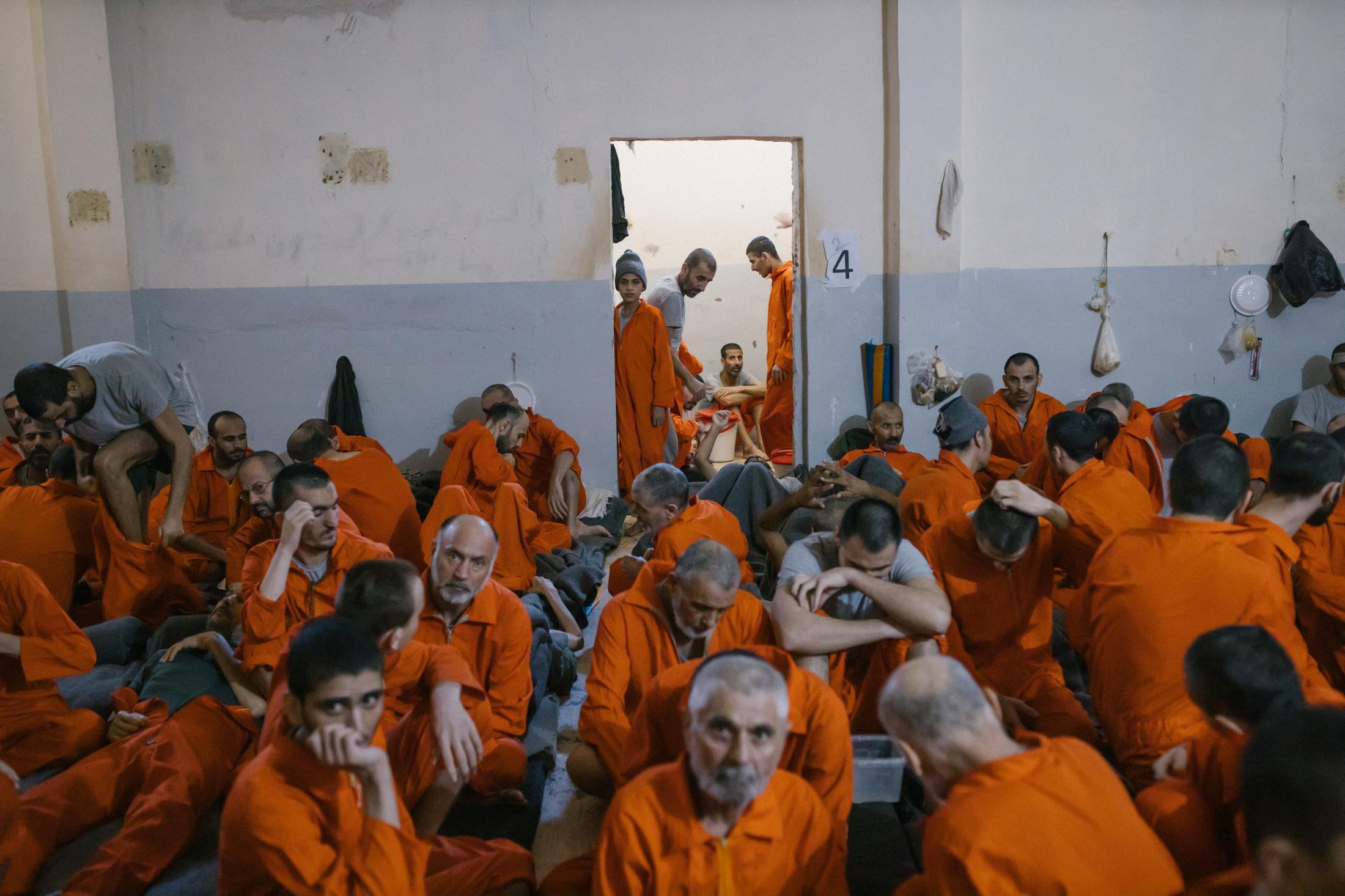 Le 30 octobre 2019, Hassake, nord est syrien. Entre 100 et 200 détenus dans chaque salle de classe. Cette pièce est surpeuplée.Les prisonniers sont considérés comme les plus radicaux et vivent dans des conditions difficiles. Ils ont droit à deux repas par jour. Dans cette pièce, il n'y a pas de lumière du jour car les fenêtres ont été condamnées. Un enfant est installé dans l'encablure de la porte. Il est mélangé aux adultes.