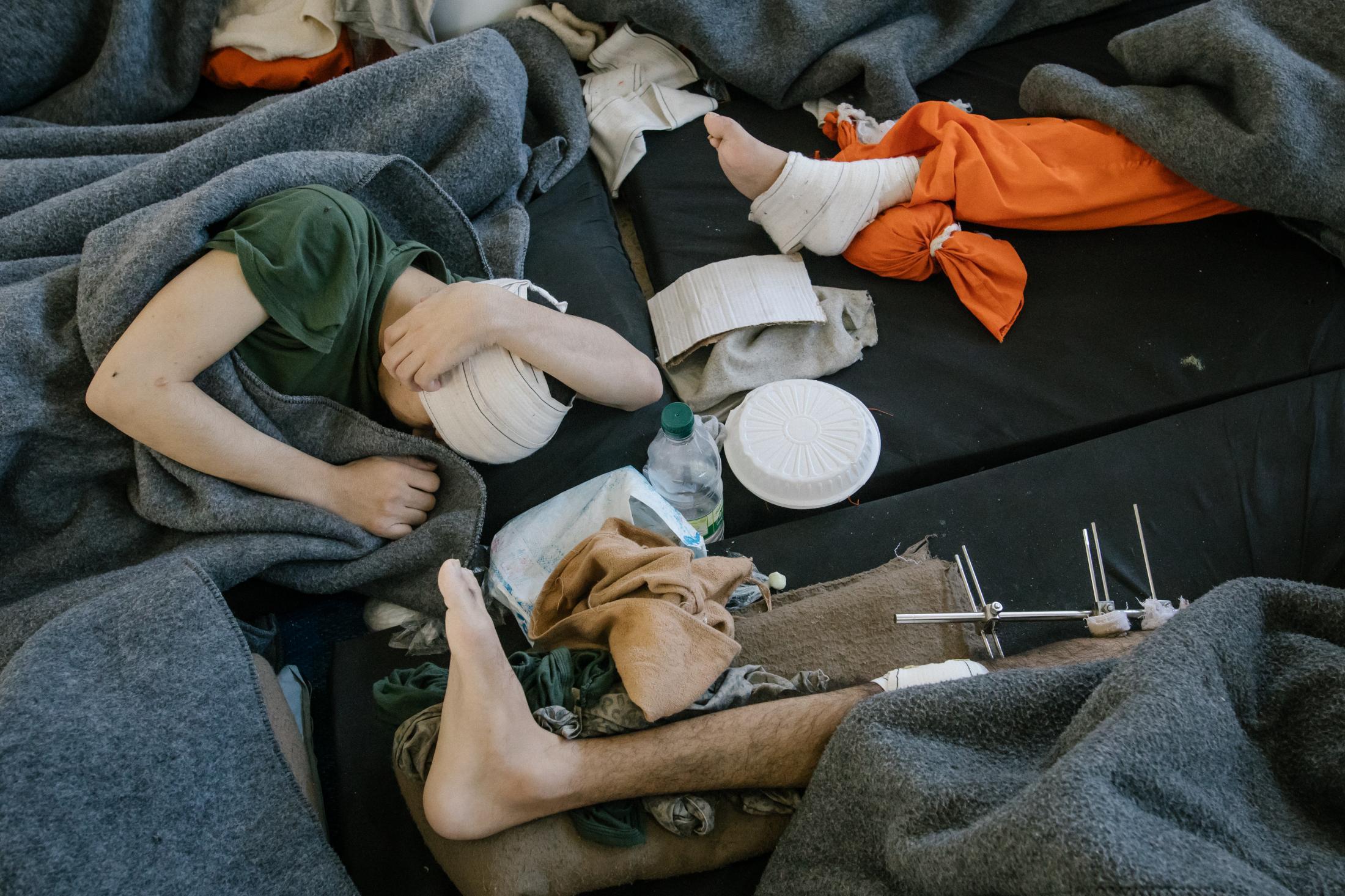 Le 30 octobre 2019, Hassake, nord est syrien. Envion 5000 prisonniers supposés membres de l'Etat islamique vivent dans cette université transformée en prison. Entre 100 et 200 détenus dans chaque salle de classe. La prison est ouverte depuis 4mois au moment de cette photo. Elle est surpeuplée. Les prisonniers sont considérés comme les plus radicaux et vivent dans des conditions difficiles. Cette pièce servait sans doute de grand réfectoire. elle se situe au rez d chaussé, et accueille tous les malades et mourrants. La plupart ont une blessure de guerre. Souvent les plaies se sont infectées.