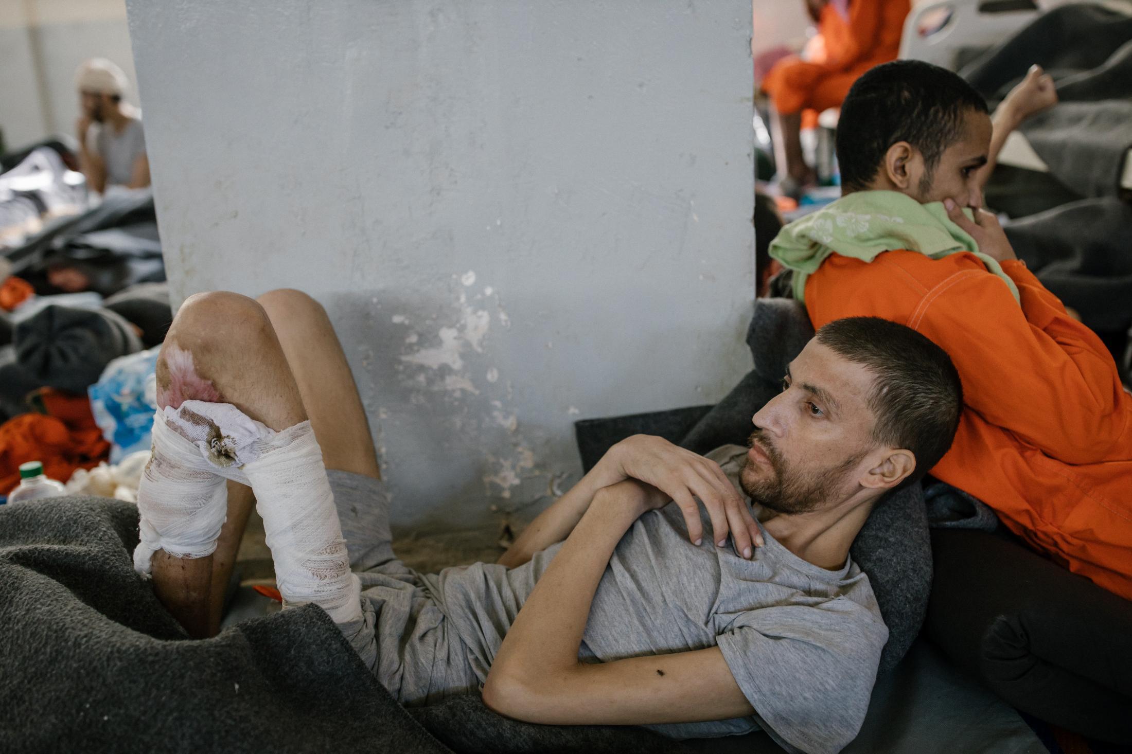 Le 30 octobre 2019, Nord Est de la Syrie. Une prison abrite des supposés membres de Daesh. Environ 5000 détenus vivraient ici. La prison est ouverte depuis 4mois. Elle est surpeuplée. Cette immense pièce sert d'hopital. Les blessés et les malades vivent ici. Les plus chanceux dorment dans un lit. D'autres sur un matelas en mousse à même le sol. Beaucoup souffrent de plaies infectées et de malnutrition comme cet homme d'origine étrangère. ( Non syrien)
