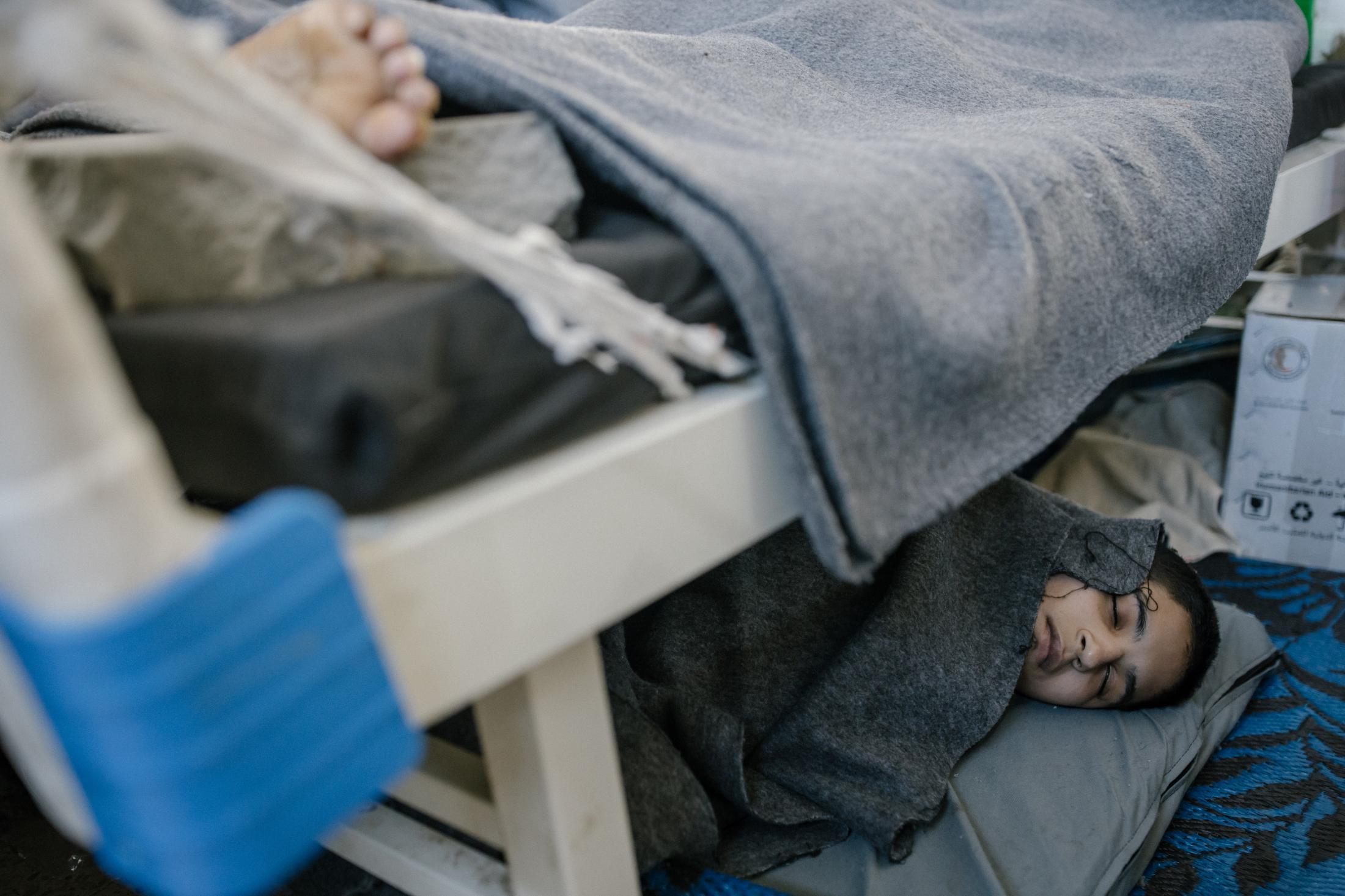 Le 30 octobre 2019, Hassake, nord est syrien. Envion 5000 prisonniers supposés membres de l'Etat islamique vivent dans cette université transformée en prison. Entre 100 et 200 détenus dans chaque salle de classe. La prison est ouverte depuis 4mois au moment de cette photo. Elle est surpeuplée. Les prisonniers sont considérés comme les plus radicaux et vivent dans des conditions difficiles. Cette pièce servait sans doute de grand réfectoire. elle se situe au rez d chaussé, et accueille tous les malades et mourrants. Les plus chanceux ont un lit, d'autres comme cet enfant, s'est trouvé une place sous un lit.