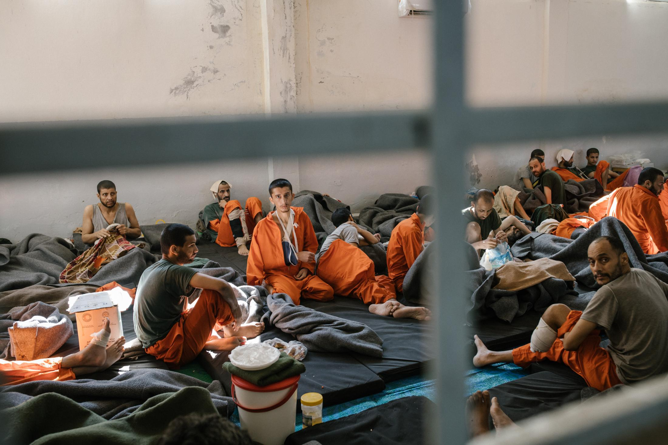 Le 30 octobre 2019, Nord Est de la Syrie. Une prison abrite des supposés membres de Daesh. Environ 5000 détenus vivraient ici. La prison est ouverte depuis 4mois. Elle est surpeuplée. Cette immense pièce sert d'hopital. Les blessés et les malades vivent ici. Les plus chanceux ont un lit, les autres dorment par terre, comme ici.