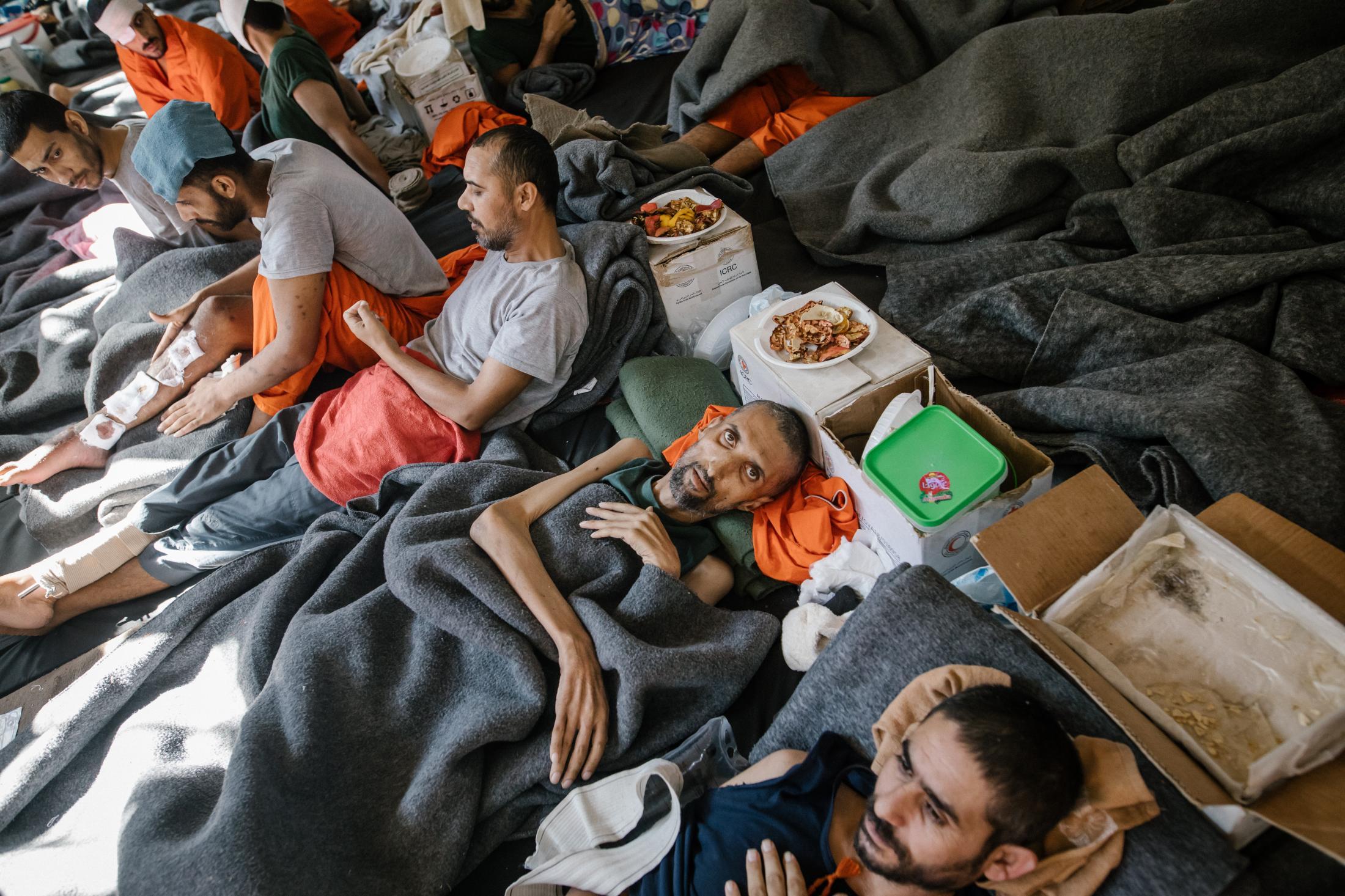 Le 30 octobre 2019, Hassake, Nord Est syrien. Environ 5000 prisonniers supposés membres de l'Etat islamique vivent dans cette université transformée en prison. Entre 100 et 200 détenus dans chaque salle de classe. La prison est ouverte depuis 4 mois au moment où cette photo a été prise. Elle est surpeuplée. Les prisonniers sont considérés comme les plus radicaux et vivent dans des conditions difficiles. Cette pièce servait sans doute de grand réfectoire avant, maintenant elle accueille les malades et mourants. Les plus chanceux ont un lit, mais cet homme qui souffre notamment de malnutrition dort par terre.