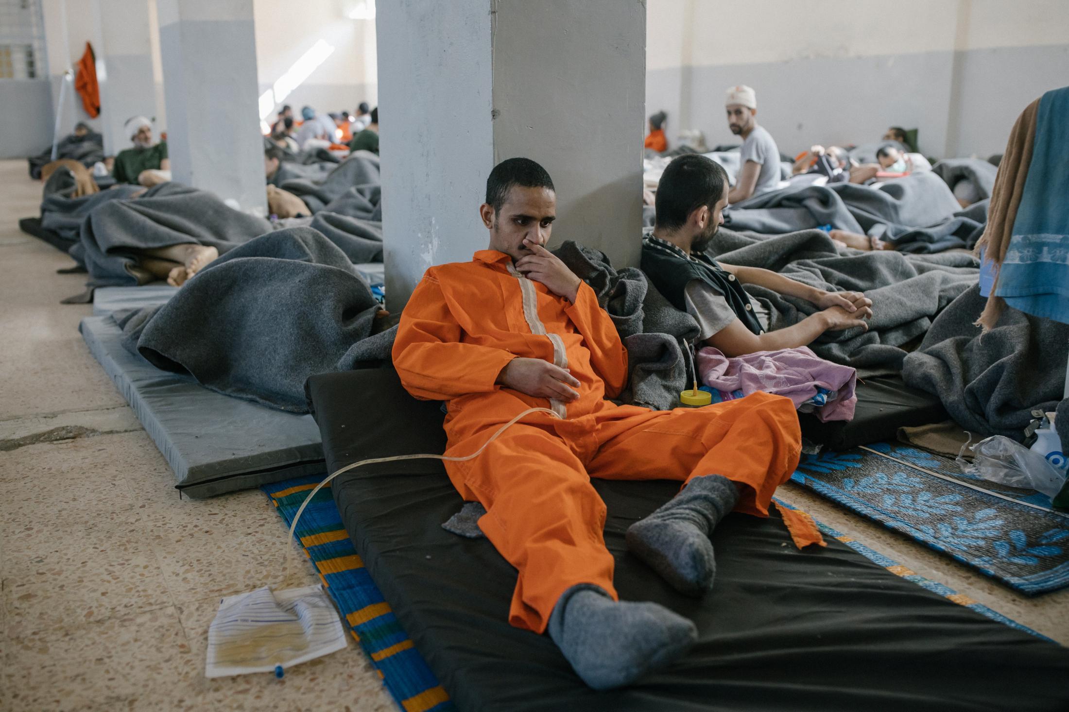Le 30 octobre 2019, Nord Est de la Syrie. Une prison abrite des supposés membres de Daesh. Environ 5000 détenus vivraient ici. La prison est ouverte depuis 4mois. Elle est surpeuplée. Cette immense pièce sert d'hopital. Les blessés et les malades vivent ici. Les plus chanceux ont un lit, les autres dorment par terre.