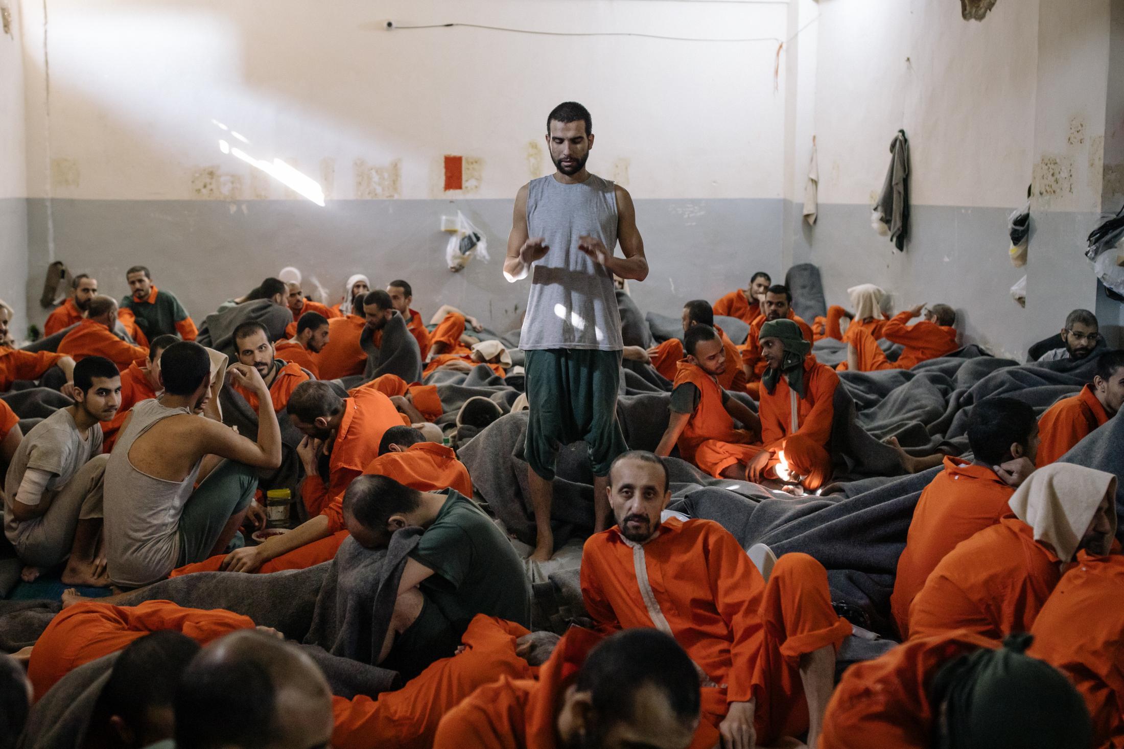Le 30 octobre 2019, Hassake, nord est syrien. Envion 5000 prisonniers supposés membres de l'Etat islamique vivent dans cette université transformée en prison. Entre 100 et 200 détenus dans chaque salle de classe. La prison est ouverte depuis 4mois au moment de cette photo. Elle est surpeuplée. Les prisonniers sont considérés comme les plus radicaux et vivent dans des conditions difficiles. Dans l'une des pièces , un prisonnier prie.