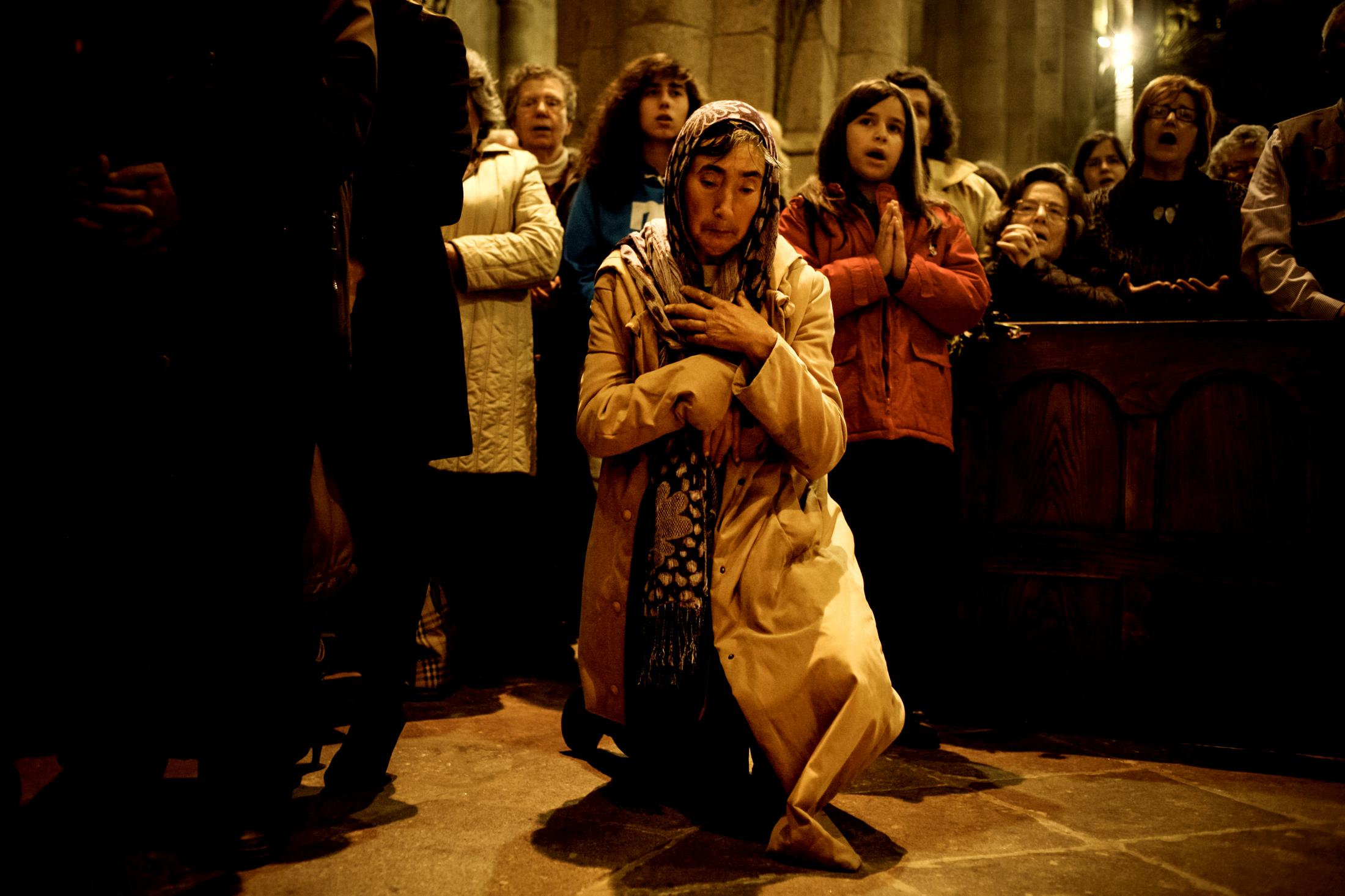 "An elderly woman prays inside Braga Cathedral, before the procession of ""Ecce Homo""."