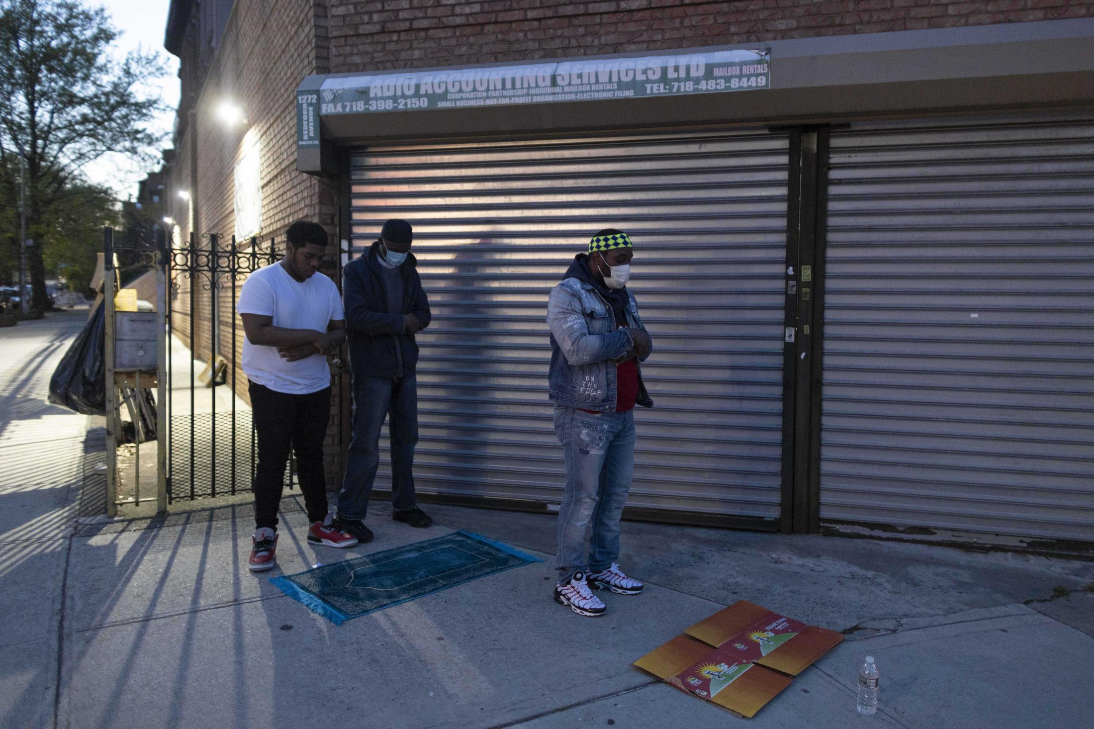 A group of muslim men praying Maghrib sunsit prayer after breaking their fast in front of At-Taqwa Mosque as the Mosque remains closed to public due to the Pandemic, Brooklyn, New York.