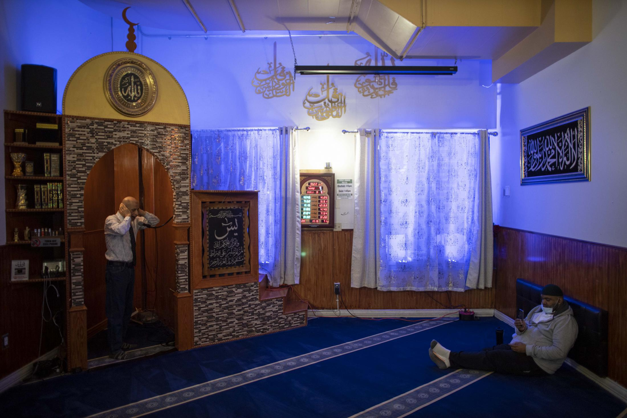 As Mosque remains closed to public, a volunteer calls for Isha prayer in the Muslim community center of Brooklyn, New York.
