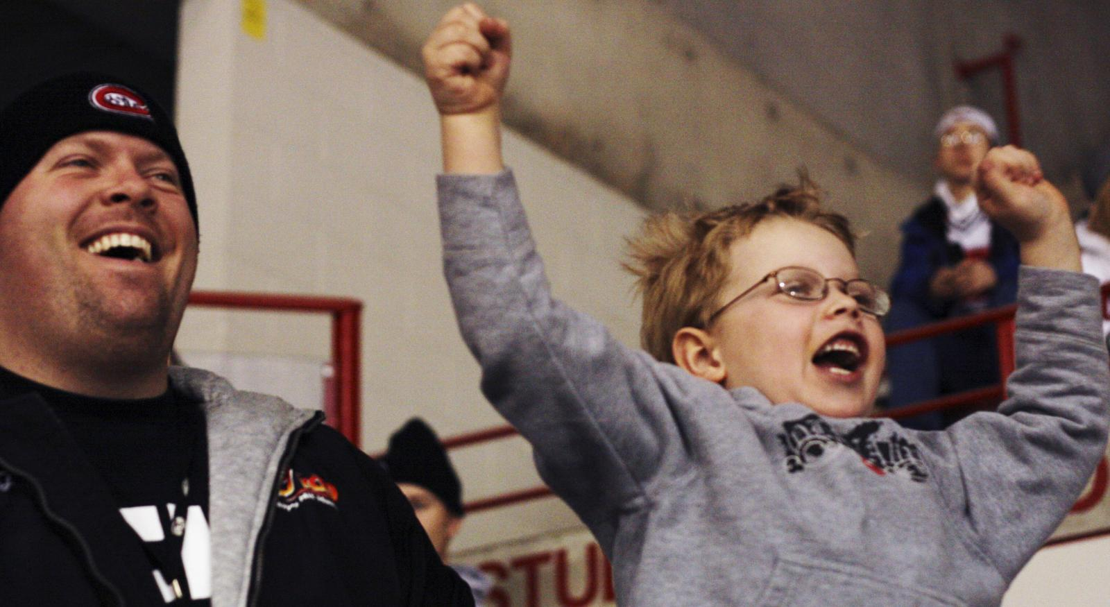 Times photo by Seungjae Seo, sseo@stcloudtimes.com JJ Holiday and his son Peygon celebrates SCSU's first goal during the Friday game at the National Hockey Center.